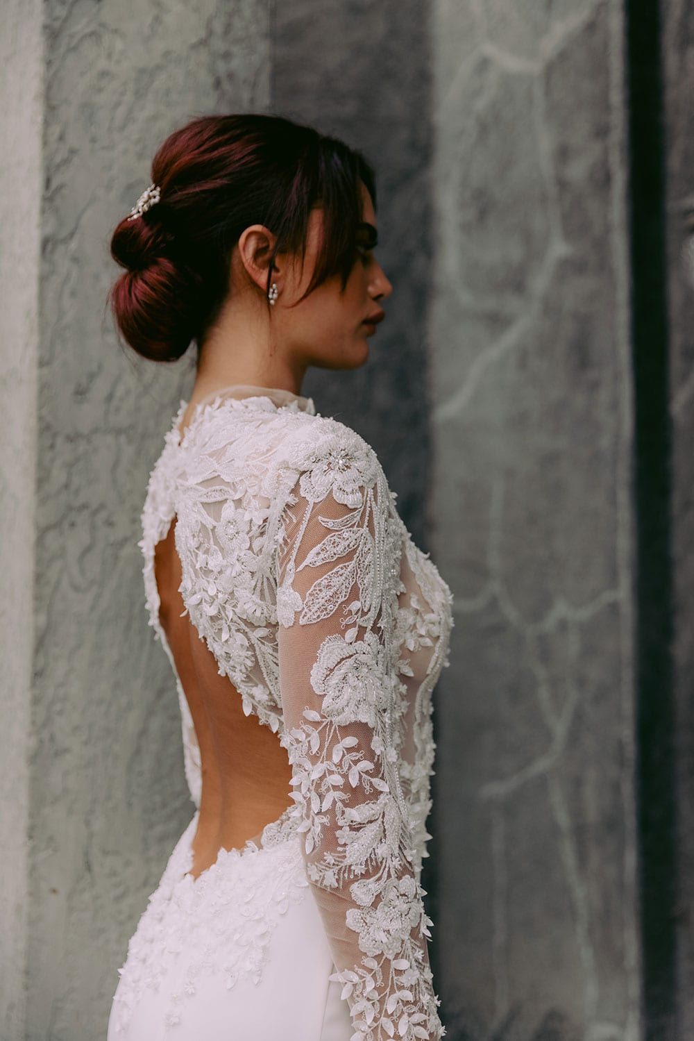 Moana Wedding gown from Vinka Design - Spectacular wedding dress perfect for the modern bride who still wants a classic spark! 3D lace embroidery complemented by a high neckline, fitted sleeves, and stunning low back into a flare train. Model wearing gown hand on hip showing top half of dress from the side.