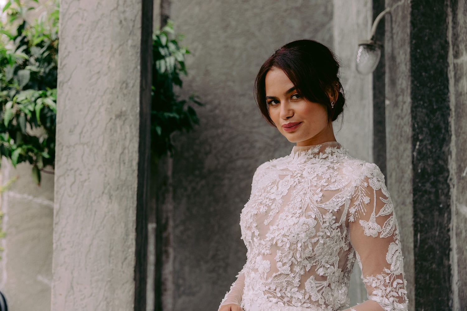 Moana Wedding gown from Vinka Design - Spectacular wedding dress perfect for the modern bride who still wants a classic spark! 3D lace embroidery complemented by a high neckline, fitted sleeves, and stunning low back into a flare train. Model wearing gown hand on hip showing top half of dress lace detail.