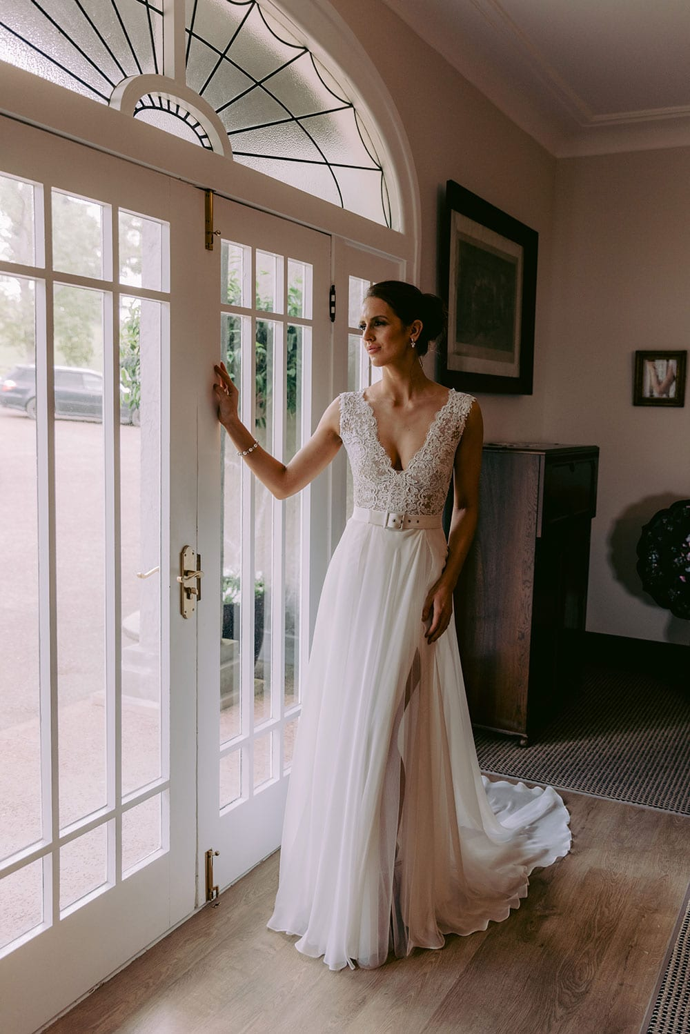 Mila Wedding gown from Vinka Design - Wedding dress with guipure lace with a deep V-shaped neckline both front and back. Skirt in bridal crepe, which gently sculpts and flatters the wearer's hips before falling into a small train. Model waring gown in brightly lit vintage room.