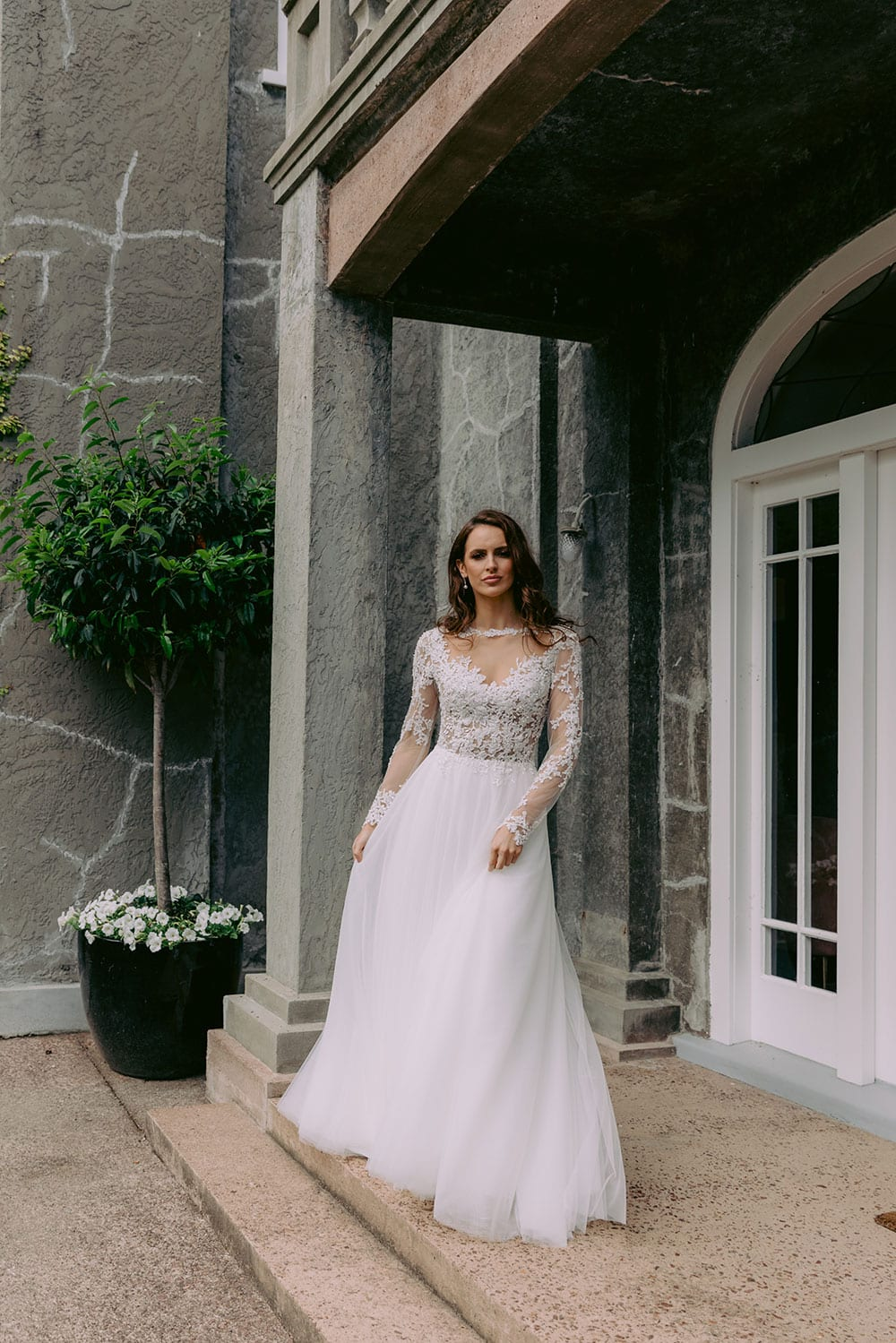 Maia Wedding gown from Vinka Design - This feminine & romantic wedding dress features beautiful pearl & bead embroidery over 3D lace. Long sleeves with pearl buttons, illusion neckline and skirt of dreamy layers of soft tulle. Model wearing gown outside heritage building in Clevedon, near Auckland.