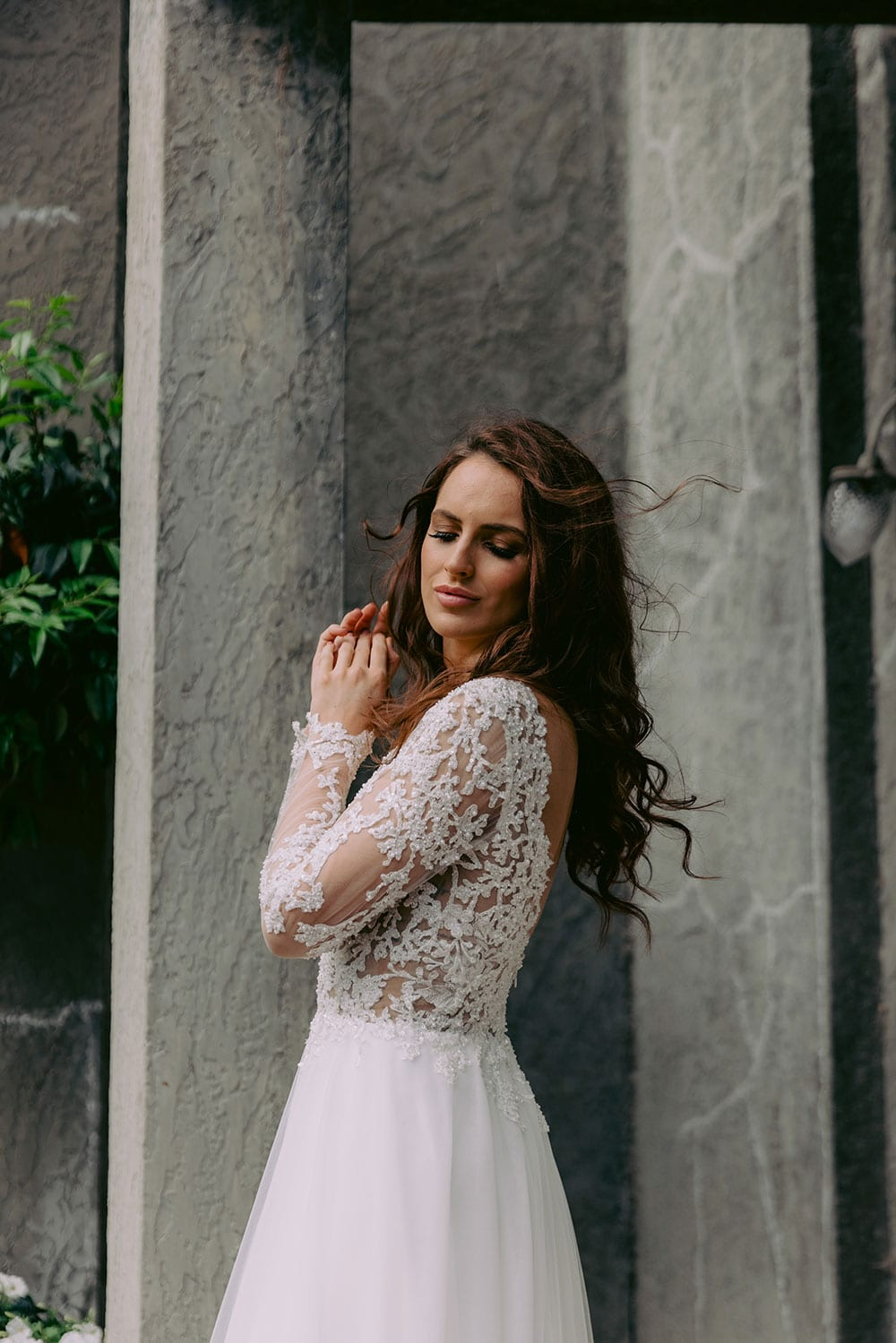 Maia Wedding gown from Vinka Design - This feminine & romantic wedding dress features beautiful pearl & bead embroidery over 3D lace. Long sleeves with pearl buttons, illusion neckline and skirt of dreamy layers of soft tulle. Model wearing gown showing long sleeve detail outside heritage building in Clevedon, near Auckland.
