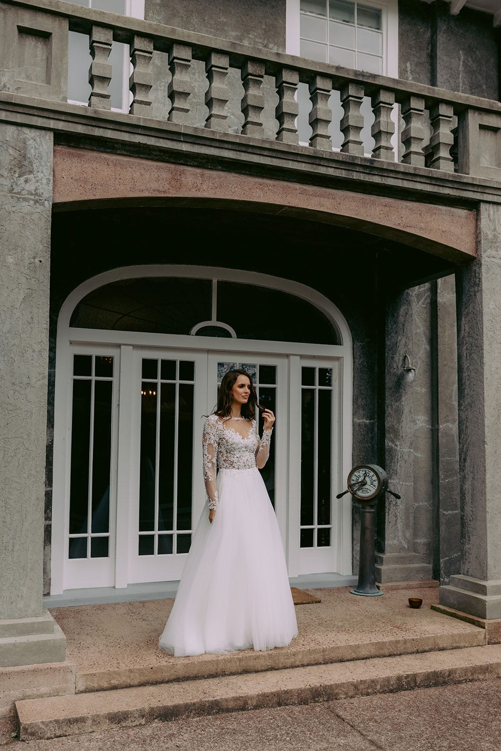 Maia Wedding gown from Vinka Design - This feminine & romantic wedding dress features beautiful pearl & bead embroidery over 3D lace. Long sleeves with pearl buttons, illusion neckline and skirt of dreamy layers of soft tulle. Model wearing gown showing full length of dress detail outside heritage building in Clevedon, near Auckland.