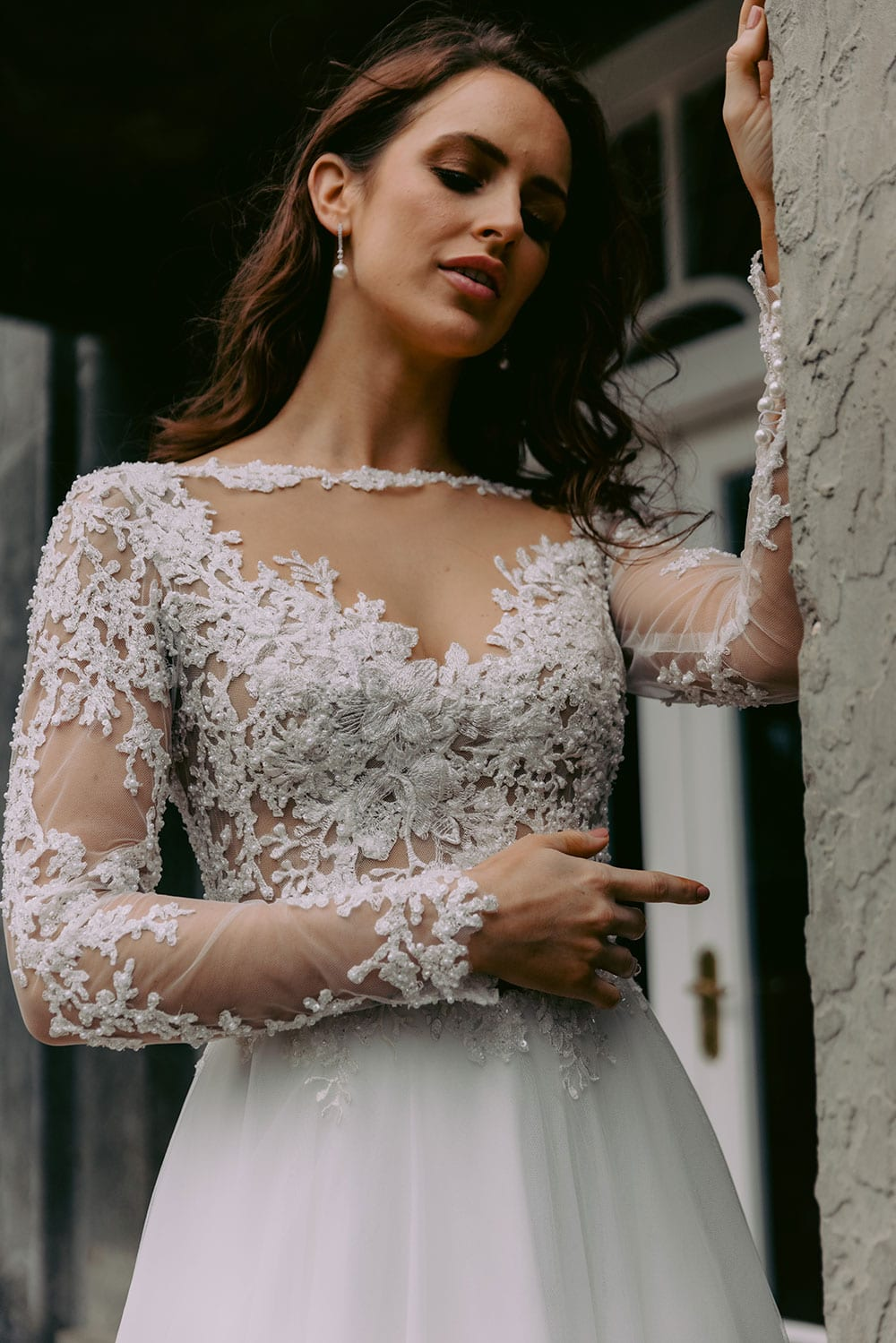 Maia Wedding gown from Vinka Design - This feminine & romantic wedding dress features beautiful pearl & bead embroidery over 3D lace. Long sleeves with pearl buttons, illusion neckline and skirt of dreamy layers of soft tulle. Model wearing gown showing lace bodice dress detail outside heritage building in Clevedon, near Auckland.