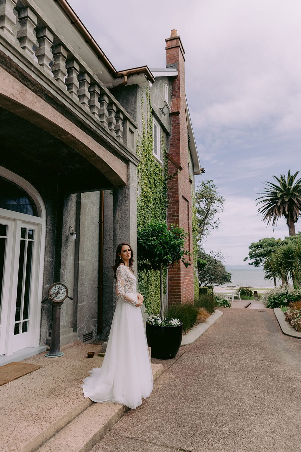 Maia Wedding gown from Vinka Design - This feminine & romantic wedding dress features beautiful pearl & bead embroidery over 3D lace. Long sleeves with pearl buttons, illusion neckline and skirt of dreamy layers of soft tulle. Model wearing gown showing full dress and dreamy skirt outside heritage building in Clevedon, near Auckland.