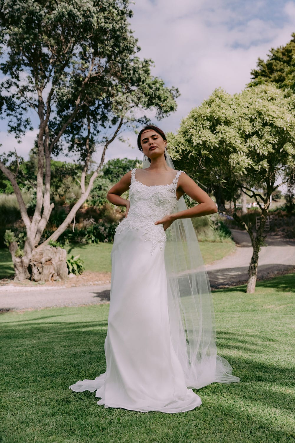 Madison Wedding gown from Vinka Design - Flattering & timeless wedding dress with lace bodice that trails into a dreamy A-line silk chiffon skirt. Illusion neckline with lace trailing up the shoulder and decorating the back. Model wearing gown with veil in gardens showing full dress.