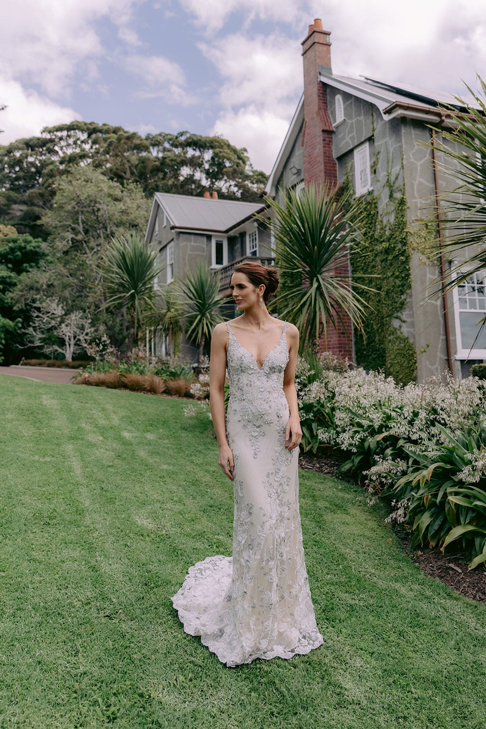 Kazumi Wedding gown from Vinka Design - Flattering and form fitting wedding dress in soft grey shades on a blush base. Low sheer back is adorned with hand-appliqued lace, bodice has a deep V-neckline, & thin straps that compliment the shoulders. Model wearing gown walking through Clevedon gardens showing low front of dress with train flowing behind.