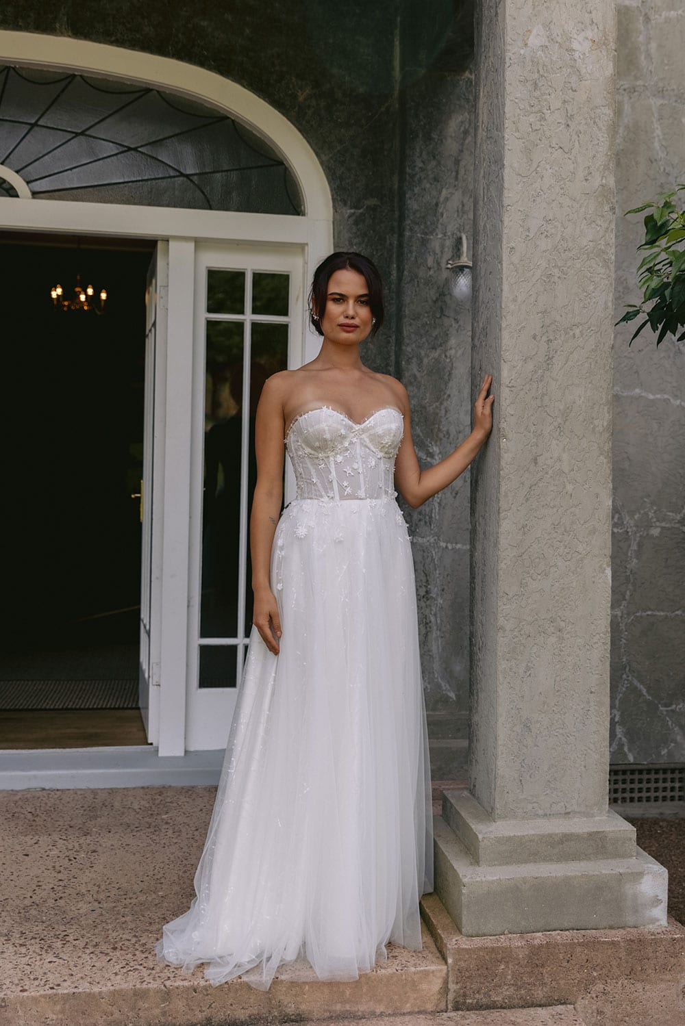 Hikari Wedding gown from Vinka Design - This modern wedding dress has a structured semi-sheer bodice with hand-appliqued lace of stars and flowers. The skirt is made with multiple layers of soft tulle. Model wearing gown in grand entrance to old building in Clevedon, near Auckland.