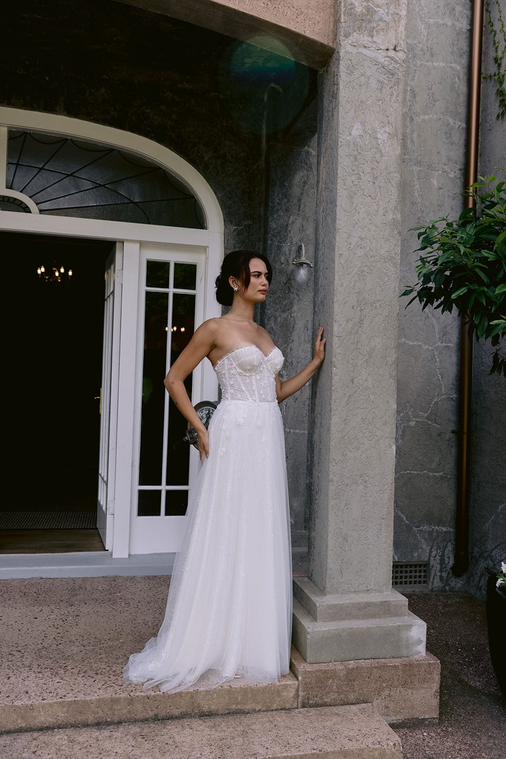 Hikari Wedding gown from Vinka Design - This modern wedding dress has a structured semi-sheer bodice with hand-appliqued lace of stars and flowers. The skirt is made with multiple layers of soft tulle. Model wearing gown in entrance to old building in Clevedon, near Auckland.