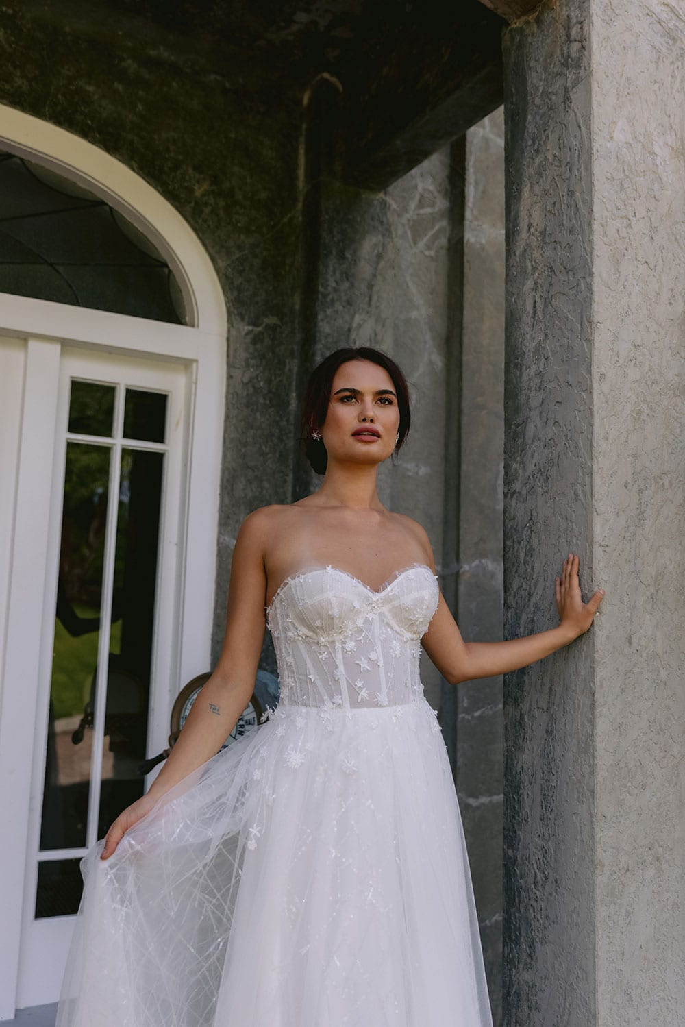 Hikari Wedding gown from Vinka Design - This modern wedding dress has a structured semi-sheer bodice with hand-appliqued lace of stars and flowers. The skirt is made with multiple layers of soft tulle. Model wearing gown holding skirt out in entrance to old building in Clevedon, near Auckland.