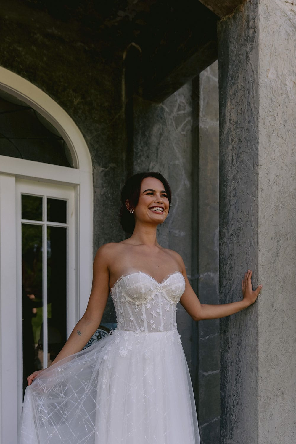Hikari Wedding gown from Vinka Design - This modern wedding dress has a structured semi-sheer bodice with hand-appliqued lace of stars and flowers. The skirt is made with multiple layers of soft tulle. Model wearing gown holding skirt out in entrance to old building near Auckland.