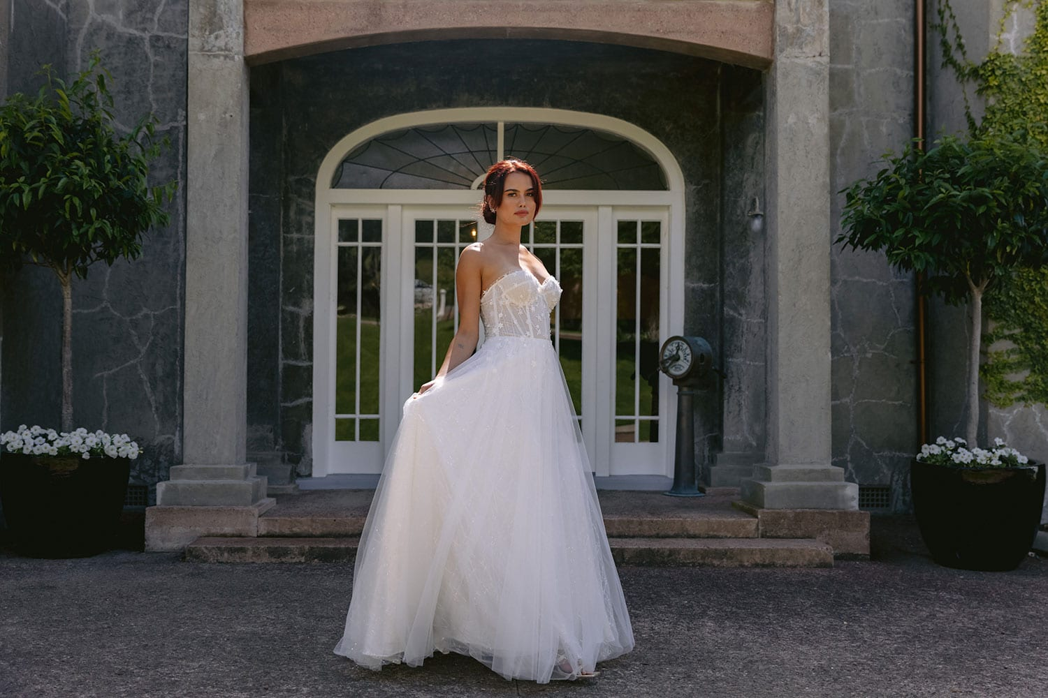 Hikari Wedding gown from Vinka Design - This modern wedding dress has a structured semi-sheer bodice with hand-appliqued lace of stars and flowers. The skirt is made with multiple layers of soft tulle. Model wearing gown holding skirt out in courtyard of old building near Auckland.