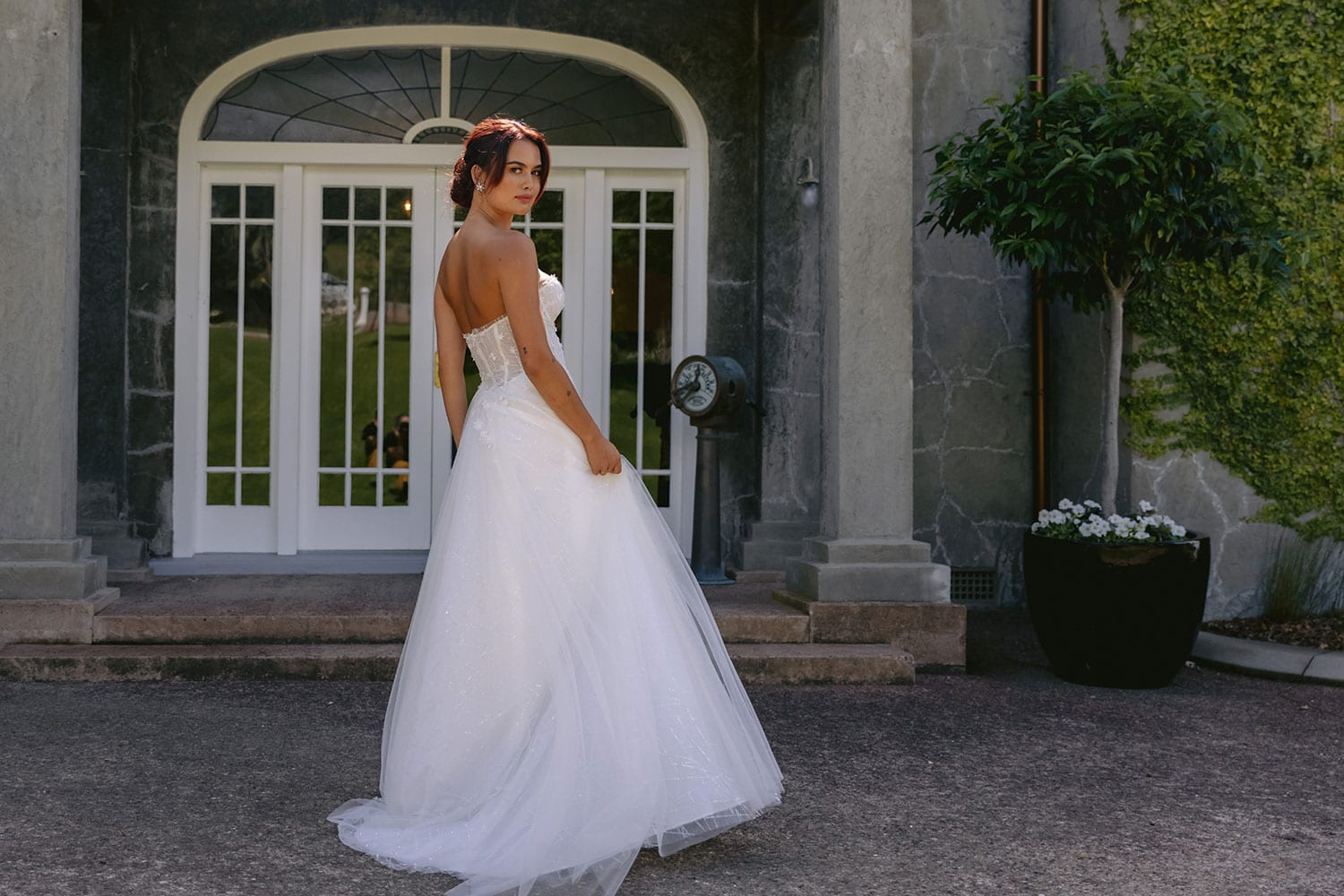 Hikari Wedding gown from Vinka Design - This modern wedding dress has a structured semi-sheer bodice with hand-appliqued lace of stars and flowers. The skirt is made with multiple layers of soft tulle. Model wearing gown showing back of dress in courtyard of old building near Auckland.