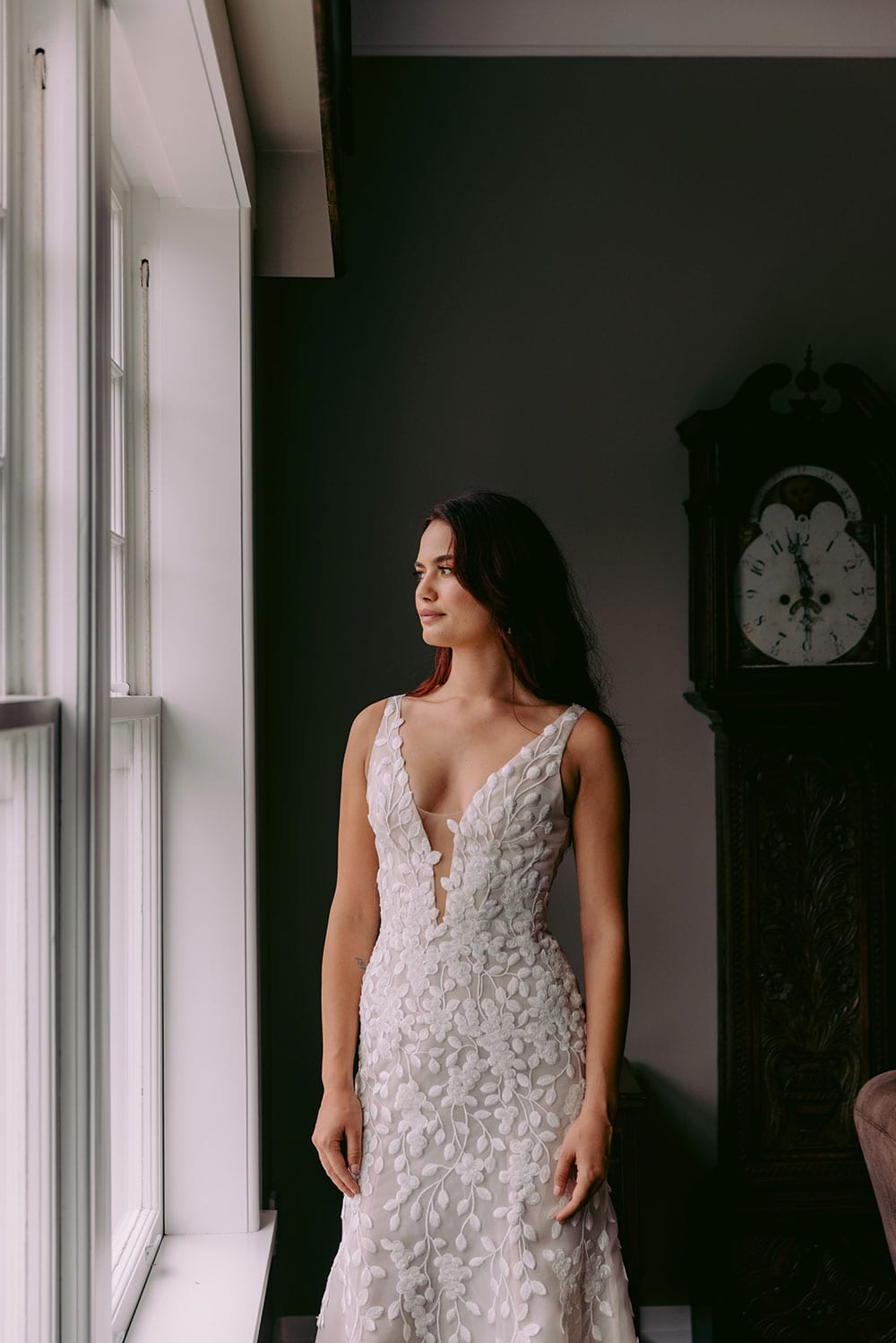 Fleur Wedding gown from Vinka Design - This gorgeous lace wedding dress is available in blush or ivory satin organza. Beautiful embroidered leaf lace, intricately cut and sewn by hand, adorn the bodice & straps and into a soft, flared train. Model wearing gown next to full windows highlighting dress.