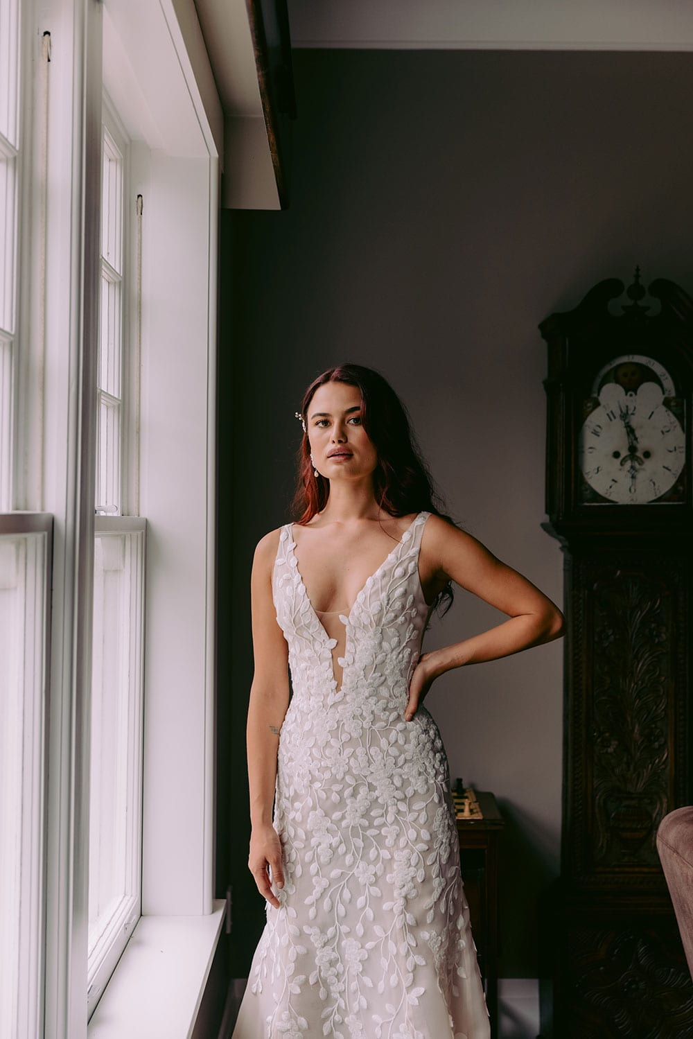 Fleur Wedding gown from Vinka Design - This gorgeous lace wedding dress is available in blush or ivory satin organza. Beautiful embroidered leaf lace, intricately cut and sewn by hand, adorn the bodice & straps and into a soft, flared train. Model wearing gown hand on hip next to full windows highlighting dress.