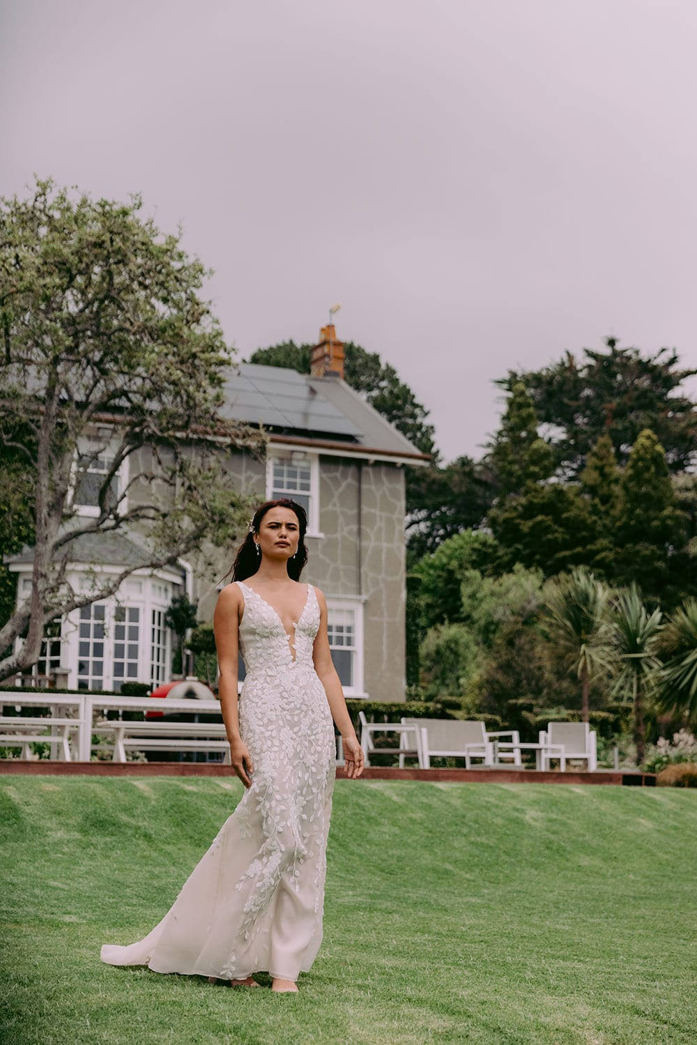 Fleur Wedding gown from Vinka Design - This gorgeous lace wedding dress is available in blush or ivory satin organza. Beautiful embroidered leaf lace, intricately cut and sewn by hand, adorn the bodice & straps and into a soft, flared train. Model wearing gown in Clevedon gardens, near Auckland.