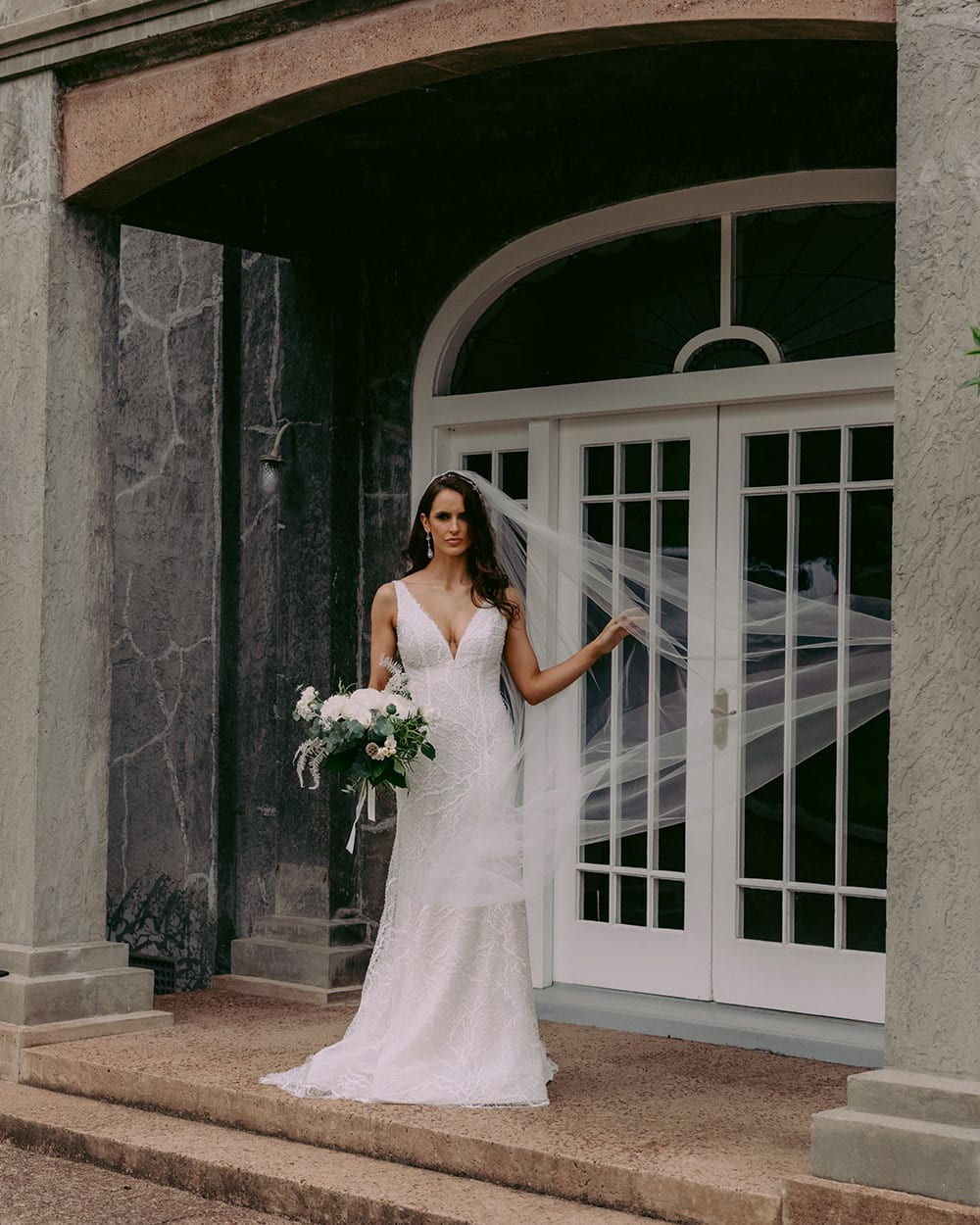 Farrah Wedding gown from Vinka Design - This beautiful wedding dress is constructed with fully beaded embroidered lace on a stretch base. V-neckline with a low, square back cut in a fit-and-flare style, which gently sculpts and enhances curves. Model wearing gown with veil.