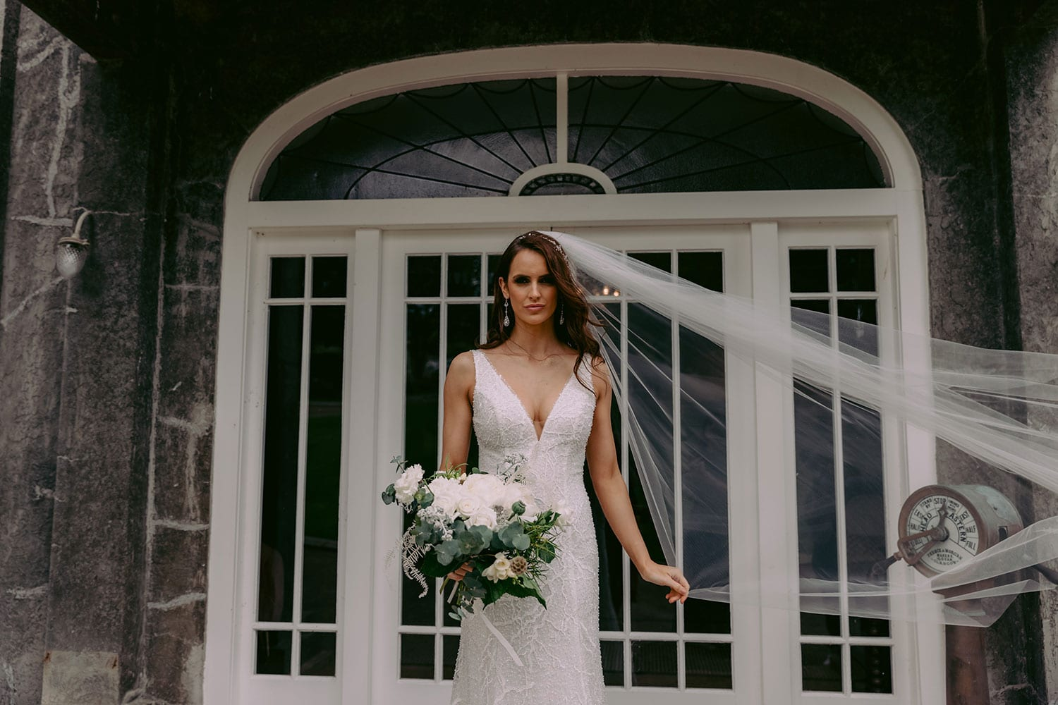 Farrah Wedding gown from Vinka Design - This beautiful wedding dress is constructed with fully beaded embroidered lace on a stretch base. V-neckline with a low, square back cut in a fit-and-flare style, which gently sculpts and enhances curves. Model wearing gown with veil holding bouquet.