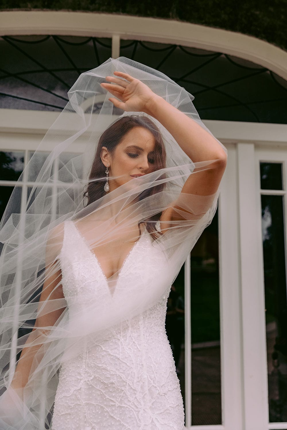 Farrah Wedding gown from Vinka Design - This beautiful wedding dress is constructed with fully beaded embroidered lace on a stretch base. V-neckline with a low, square back cut in a fit-and-flare style, which gently sculpts and enhances curves. Model wearing gown holding veil over head.