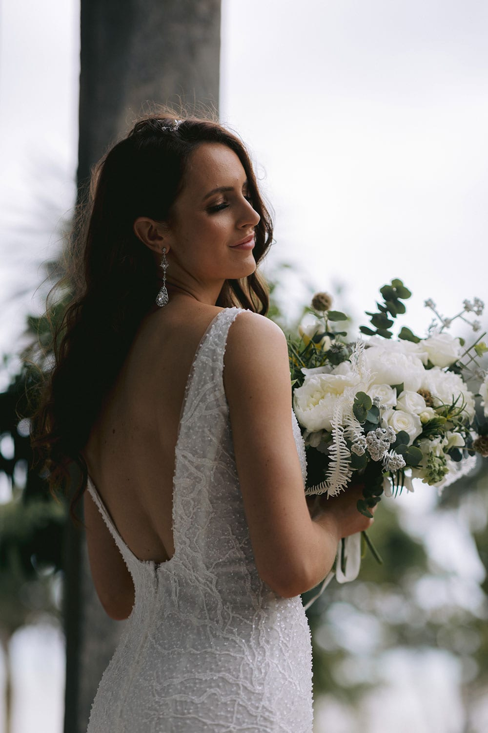 Farrah Wedding gown from Vinka Design - This beautiful wedding dress is constructed with fully beaded embroidered lace on a stretch base. V-neckline with a low, square back cut in a fit-and-flare style, which gently sculpts and enhances curves. Model wearing gown showing ow back detail.