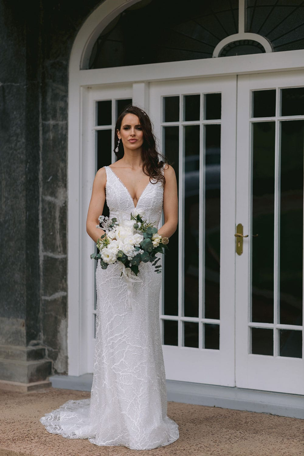 Farrah Wedding gown from Vinka Design - This beautiful wedding dress is constructed with fully beaded embroidered lace on a stretch base. V-neckline with a low, square back cut in a fit-and-flare style, which gently sculpts and enhances curves. Model wearing gown holding bouquet.