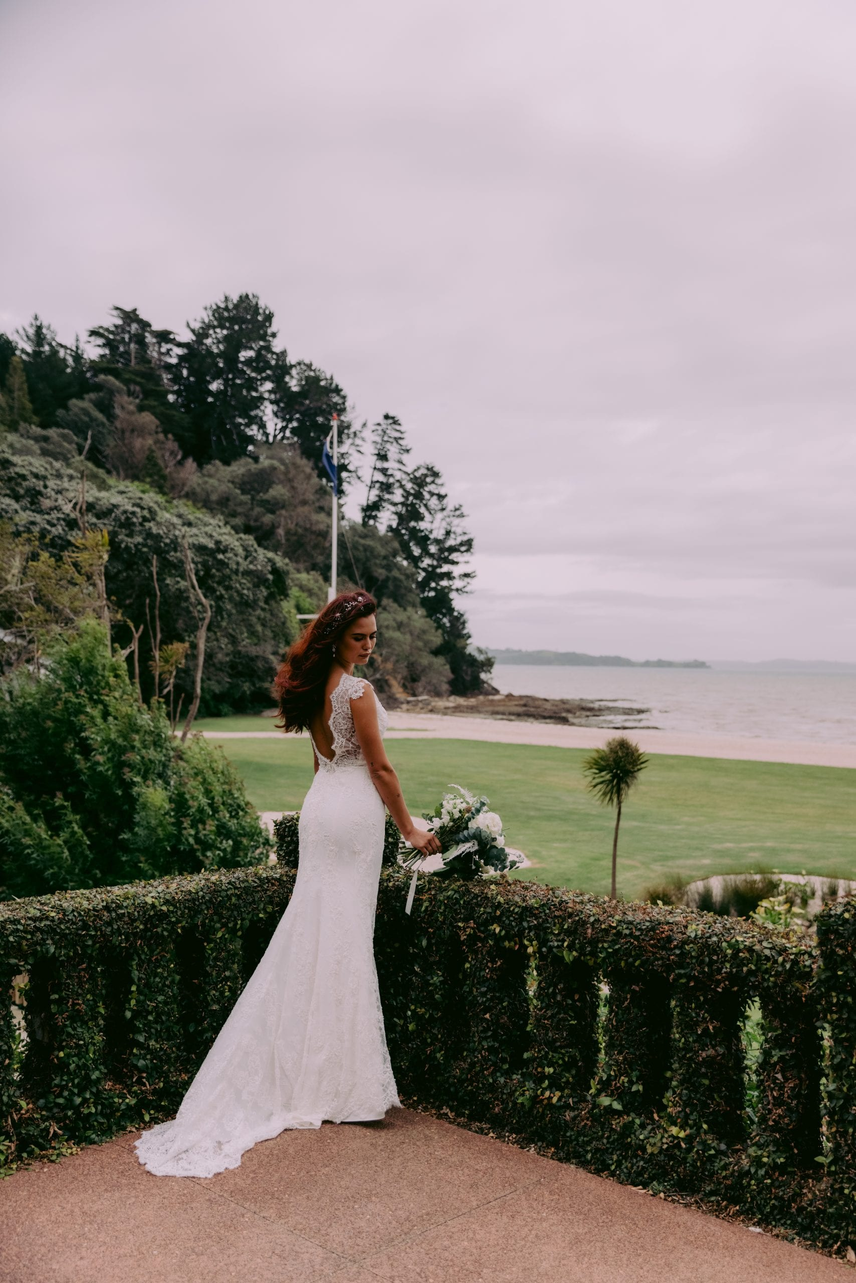 Fallyn Wedding gown from Vinka Design - This wedding dress is a timeless classic. Dramatic scallop lace and deep V-shaped neckline with beautiful low back and mini cap sleeves. This gown is cut in a fit-and-flare design with a side split. Model wearing gown in Clevedon gardens looking out to sea.