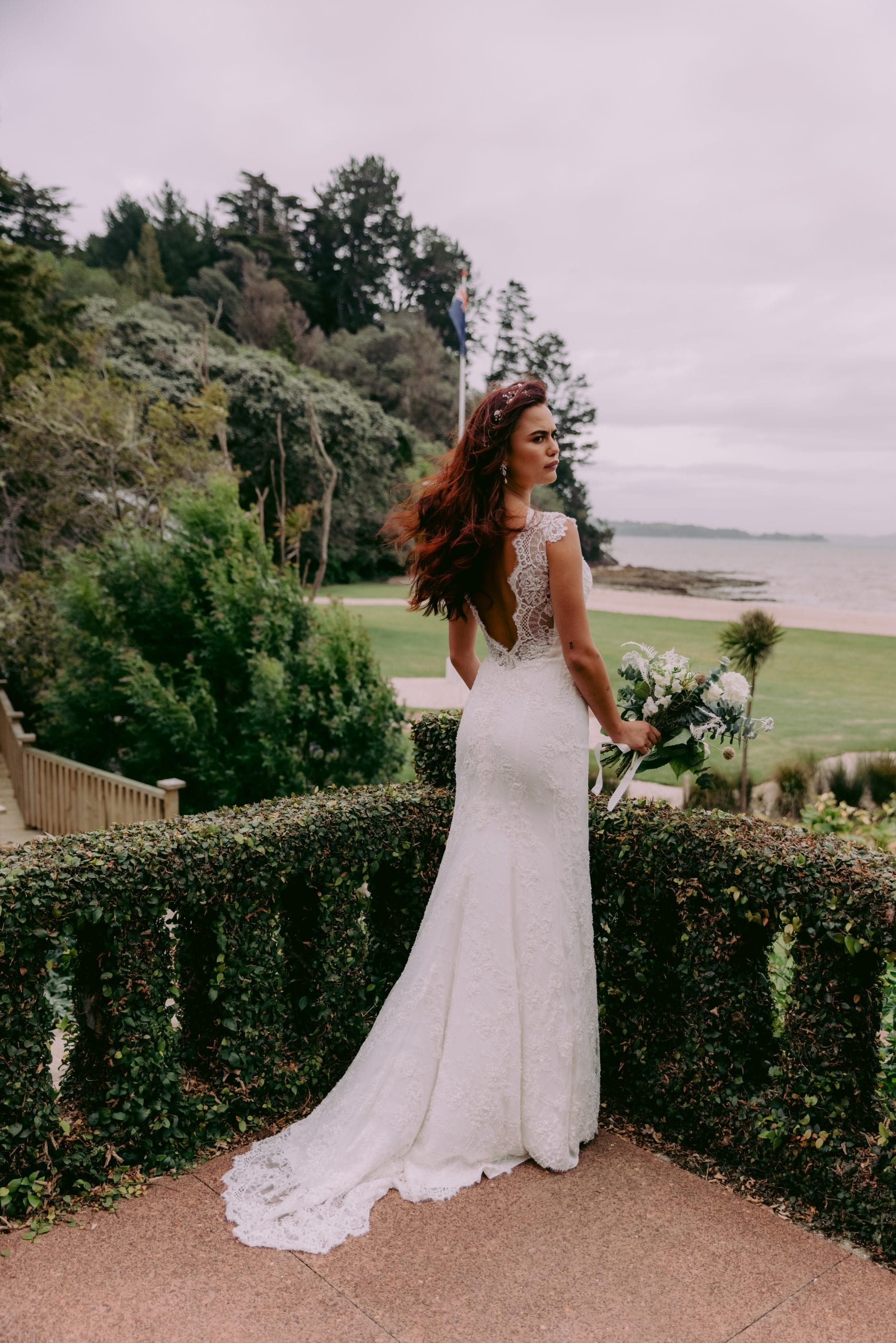Fallyn Wedding gown from Vinka Design - This wedding dress is a timeless classic. Dramatic scallop lace and deep V-shaped neckline with beautiful low back and mini cap sleeves. This gown is cut in a fit-and-flare design with a side split. Model wearing gown in Clevedon gardens with train flowing behind.