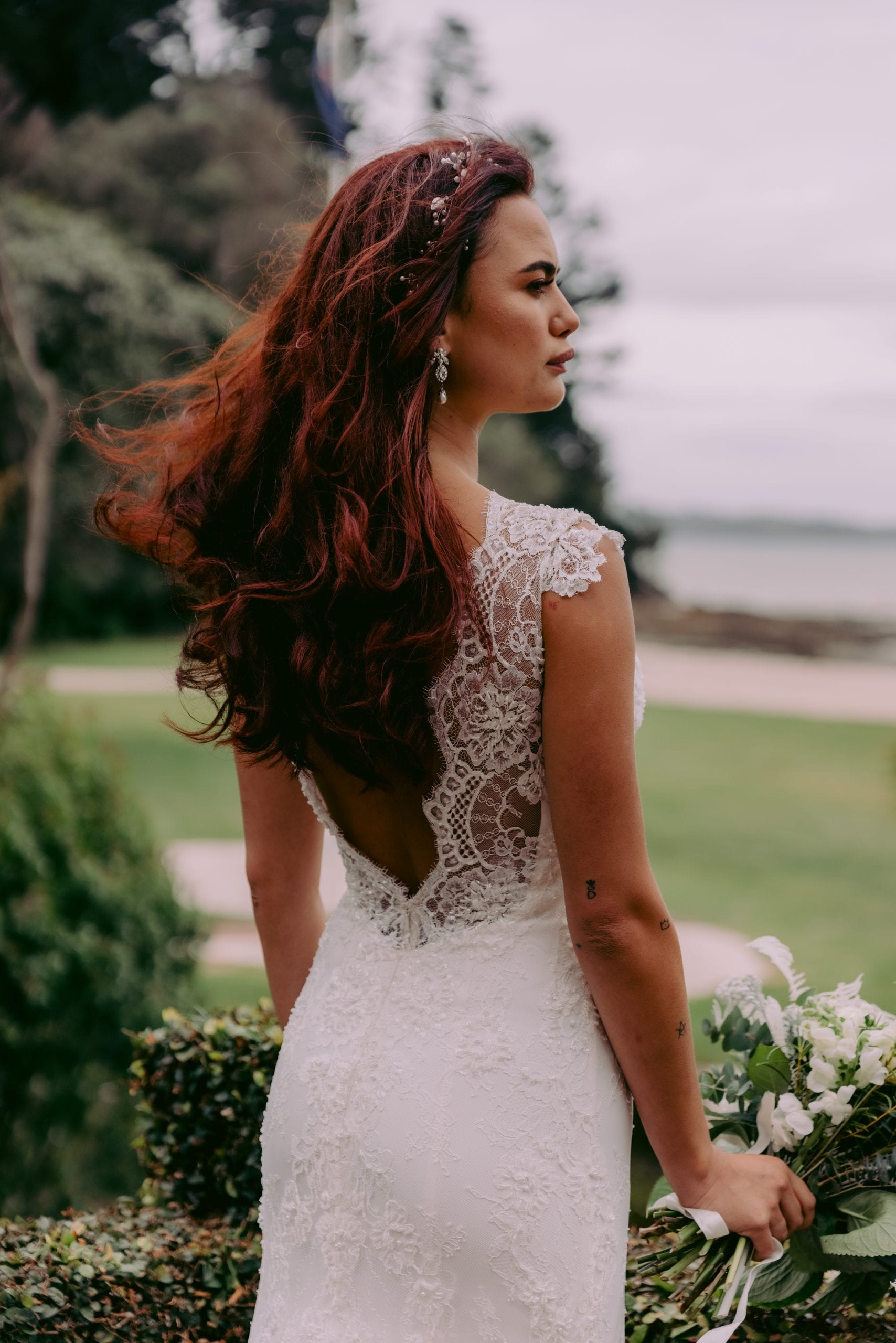 Fallyn Wedding gown from Vinka Design - This wedding dress is a timeless classic. Dramatic scallop lace and deep V-shaped neckline with beautiful low back and mini cap sleeves. This gown is cut in a fit-and-flare design with a side split. Model wearing gown , close up detail of low back.
