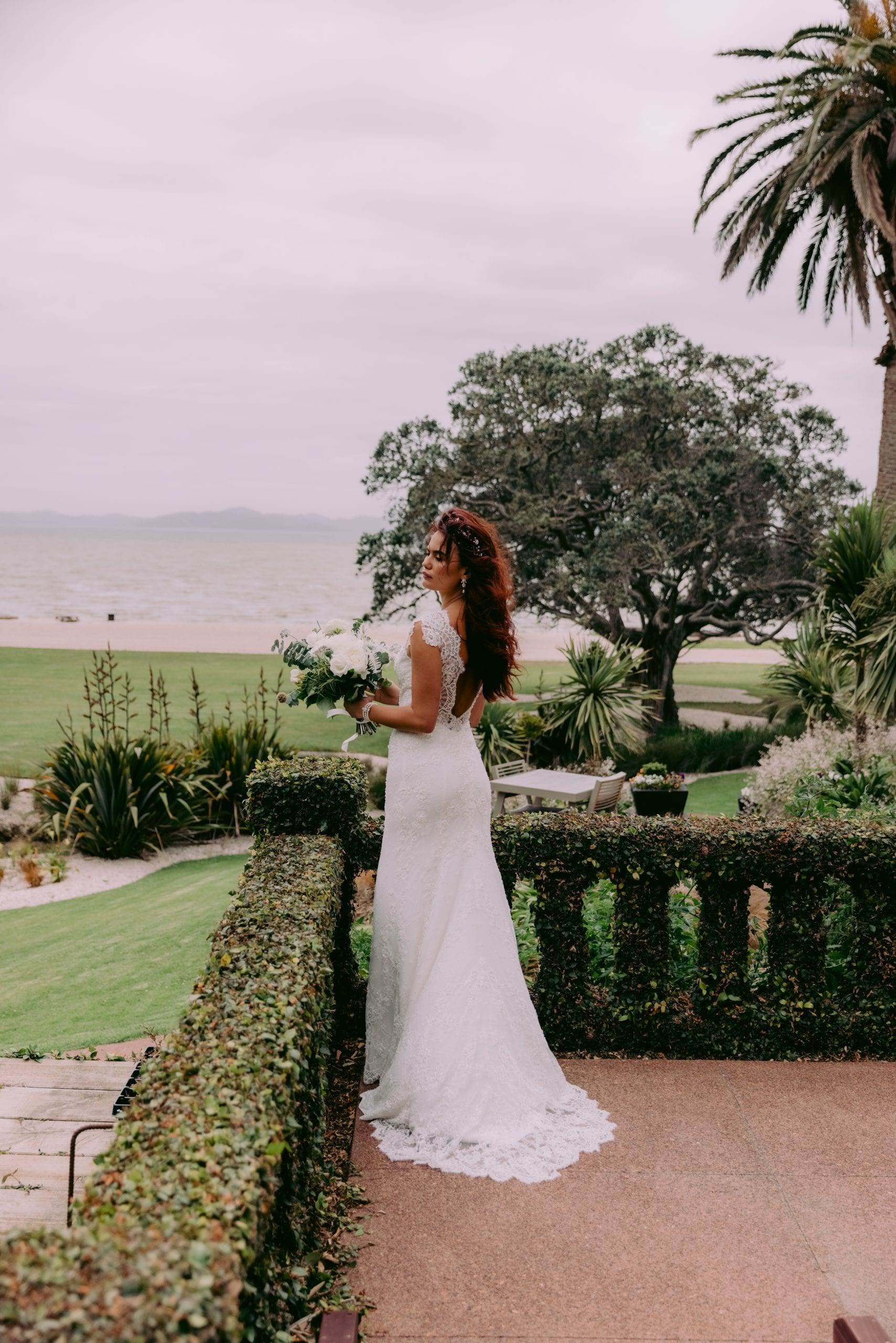 Fallyn Wedding gown from Vinka Design - This wedding dress is a timeless classic. Dramatic scallop lace and deep V-shaped neckline with beautiful low back and mini cap sleeves. This gown is cut in a fit-and-flare design with a side split. Model wearing gown showing side detail.