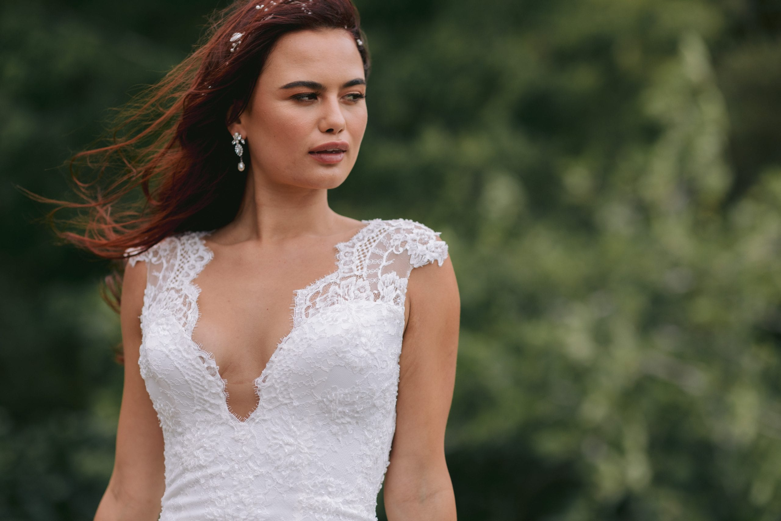 Fallyn Wedding gown from Vinka Design - This wedding dress is a timeless classic. Dramatic scallop lace and deep V-shaped neckline with beautiful low back and mini cap sleeves. This gown is cut in a fit-and-flare design with a side split. Model wearing gown showing scalloped neckline.