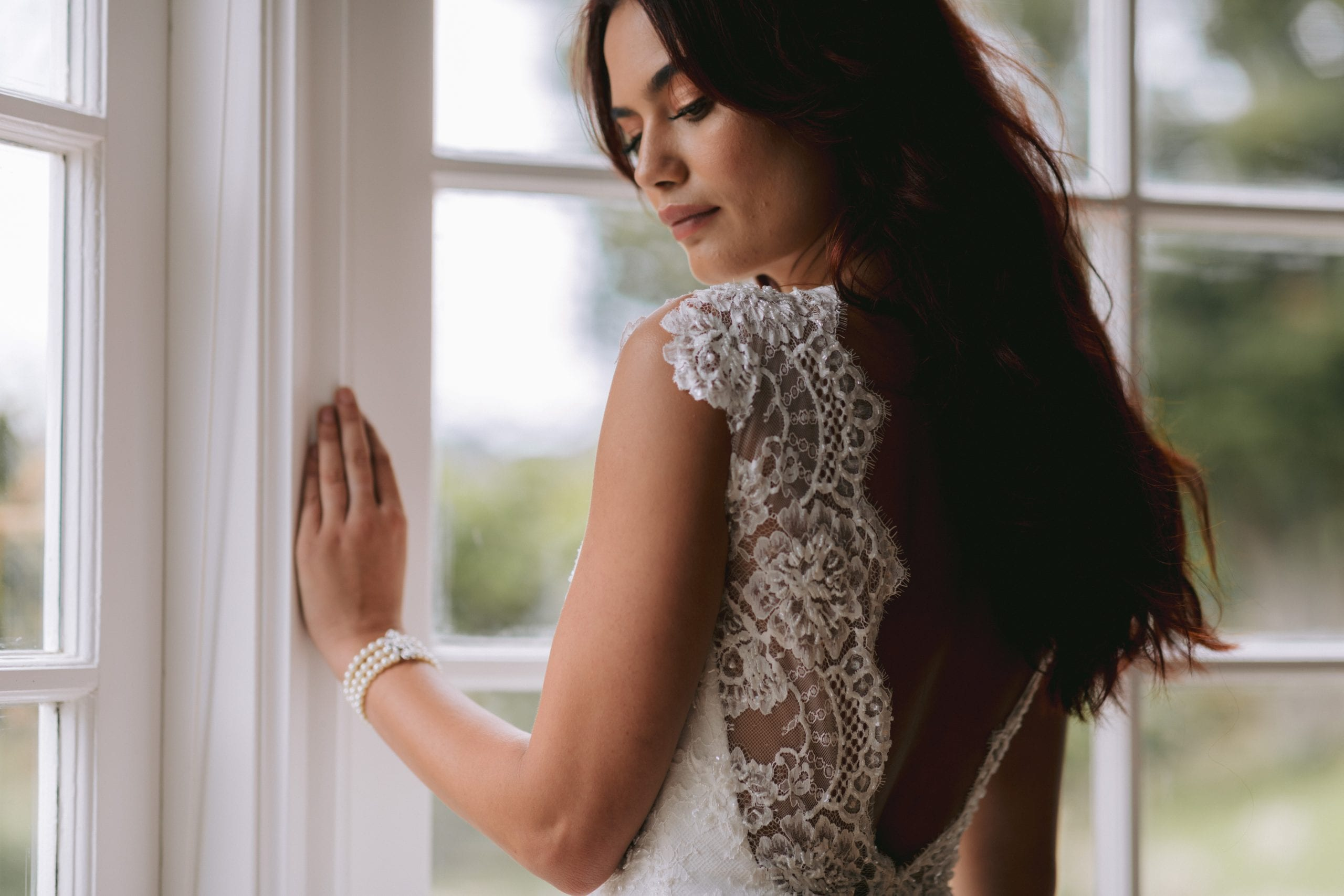 Fallyn Wedding gown from Vinka Design - This wedding dress is a timeless classic. Dramatic scallop lace and deep V-shaped neckline with beautiful low back and mini cap sleeves. This gown is cut in a fit-and-flare design with a side split. Model wearing gown showing mini cap sleeves.