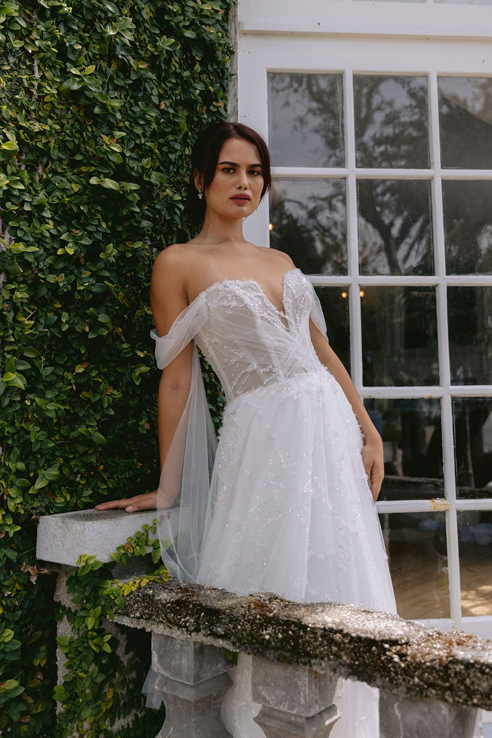 Evie Wedding gown from Vinka Design - Dreamy semi-sheer wedding dress with lace embroidery and beading. The bodice is structured, with hand-appliqued lace and draped with tulle to integrate modern elements with classic design. Model wearing gown on balcony.