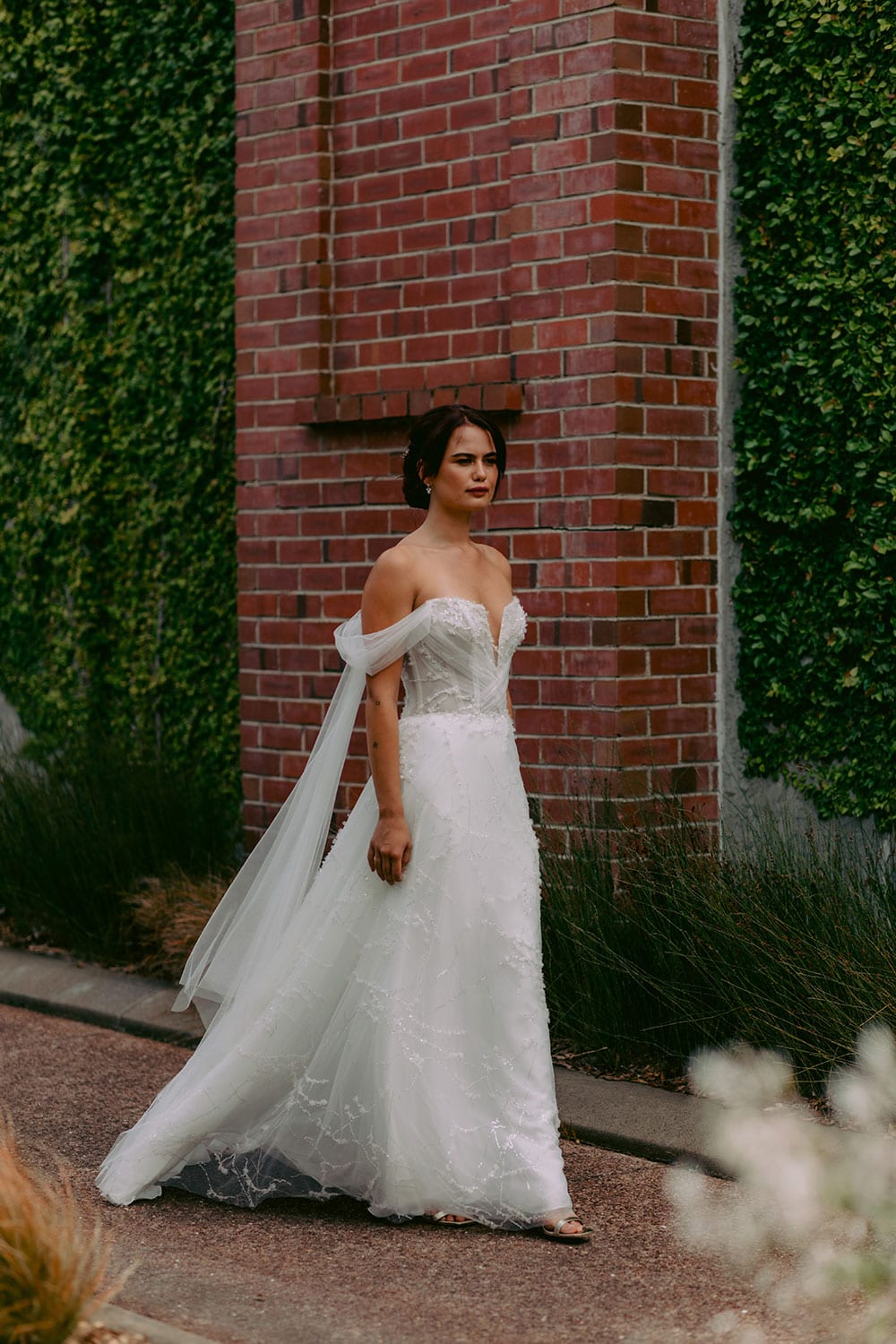 Evie Wedding gown from Vinka Design - Dreamy semi-sheer wedding dress with lace embroidery and beading. The bodice is structured, with hand-appliqued lace and draped with tulle to integrate modern elements with classic design. Model wearing gown walking in front of brick wall.