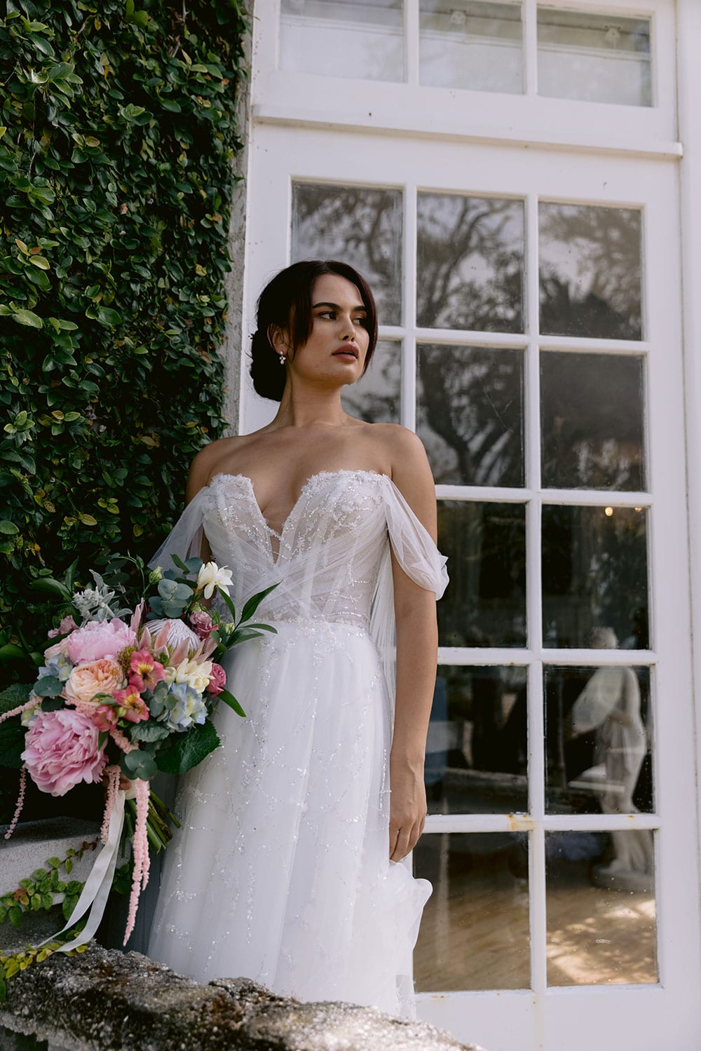 Evie Wedding gown from Vinka Design - Dreamy semi-sheer wedding dress with lace embroidery and beading. The bodice is structured, with hand-appliqued lace and draped with tulle to integrate modern elements with classic design. Model wearing gown holding bouquet.