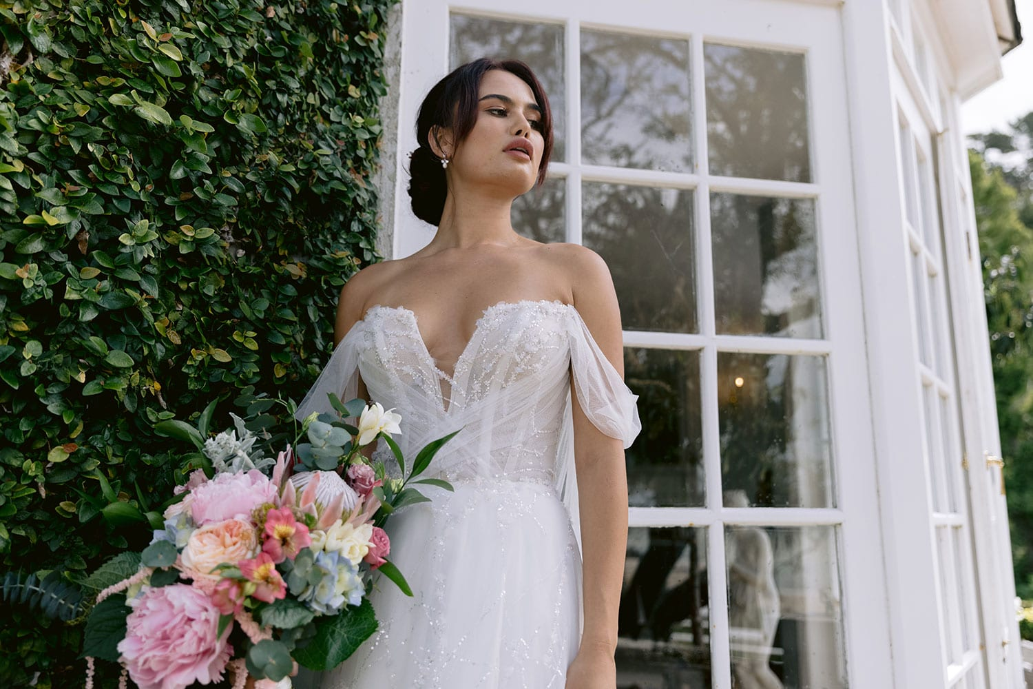 Evie Wedding gown from Vinka Design - Dreamy semi-sheer wedding dress with lace embroidery and beading. The bodice is structured, with hand-appliqued lace and draped with tulle to integrate modern elements with classic design. Model wearing gown showing front panel detail.