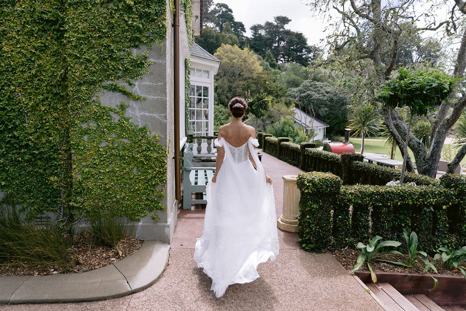 Evie Wedding gown from Vinka Design - Dreamy semi-sheer wedding dress with lace embroidery and beading. The bodice is structured, with hand-appliqued lace and draped with tulle to integrate modern elements with classic design. Model wearing gown walking showing back of dress.