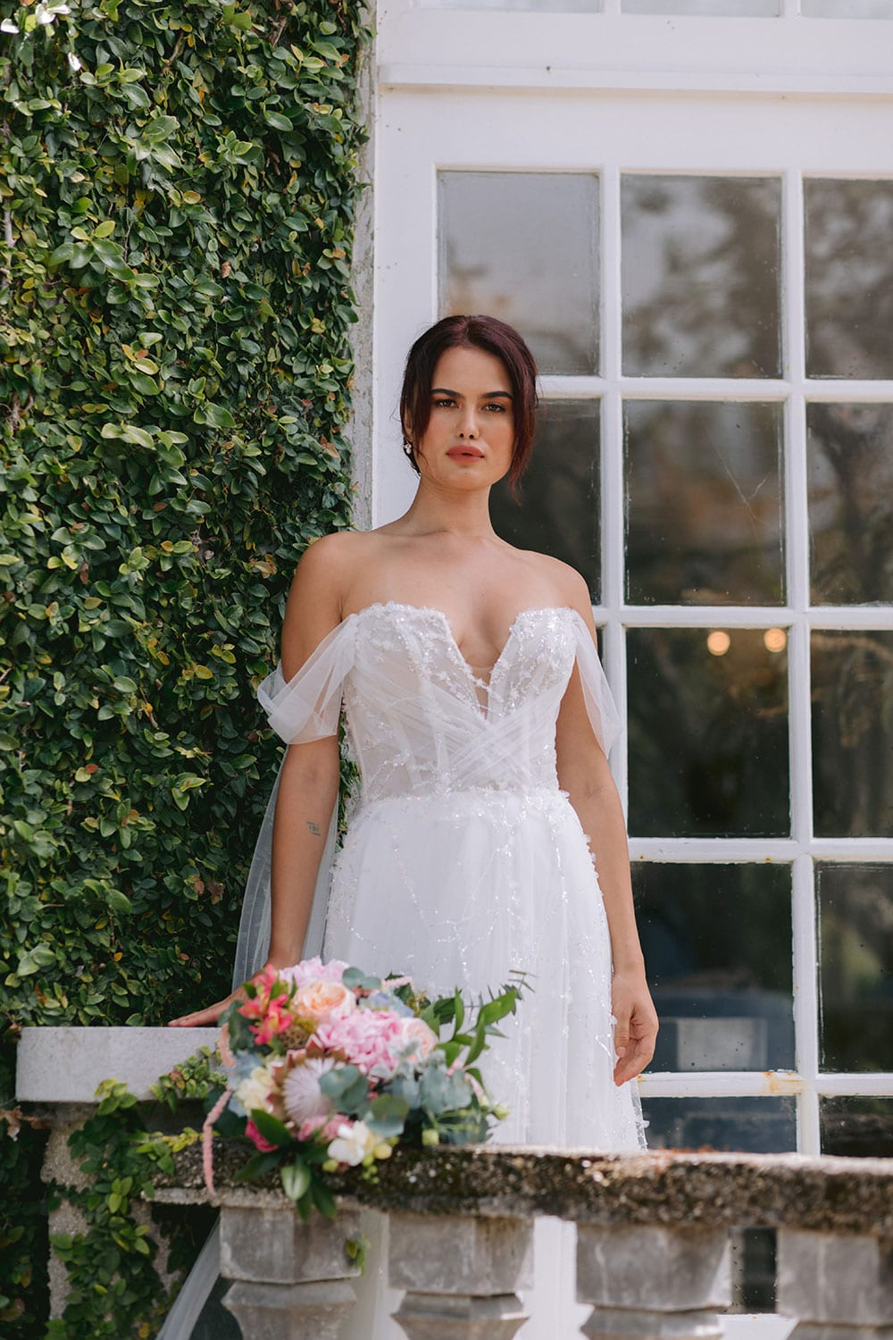 Evie Wedding gown from Vinka Design - Dreamy semi-sheer wedding dress with lace embroidery and beading. The bodice is structured, with hand-appliqued lace and draped with tulle to integrate modern elements with classic design. Model wearing gown on balcony with bouquet.