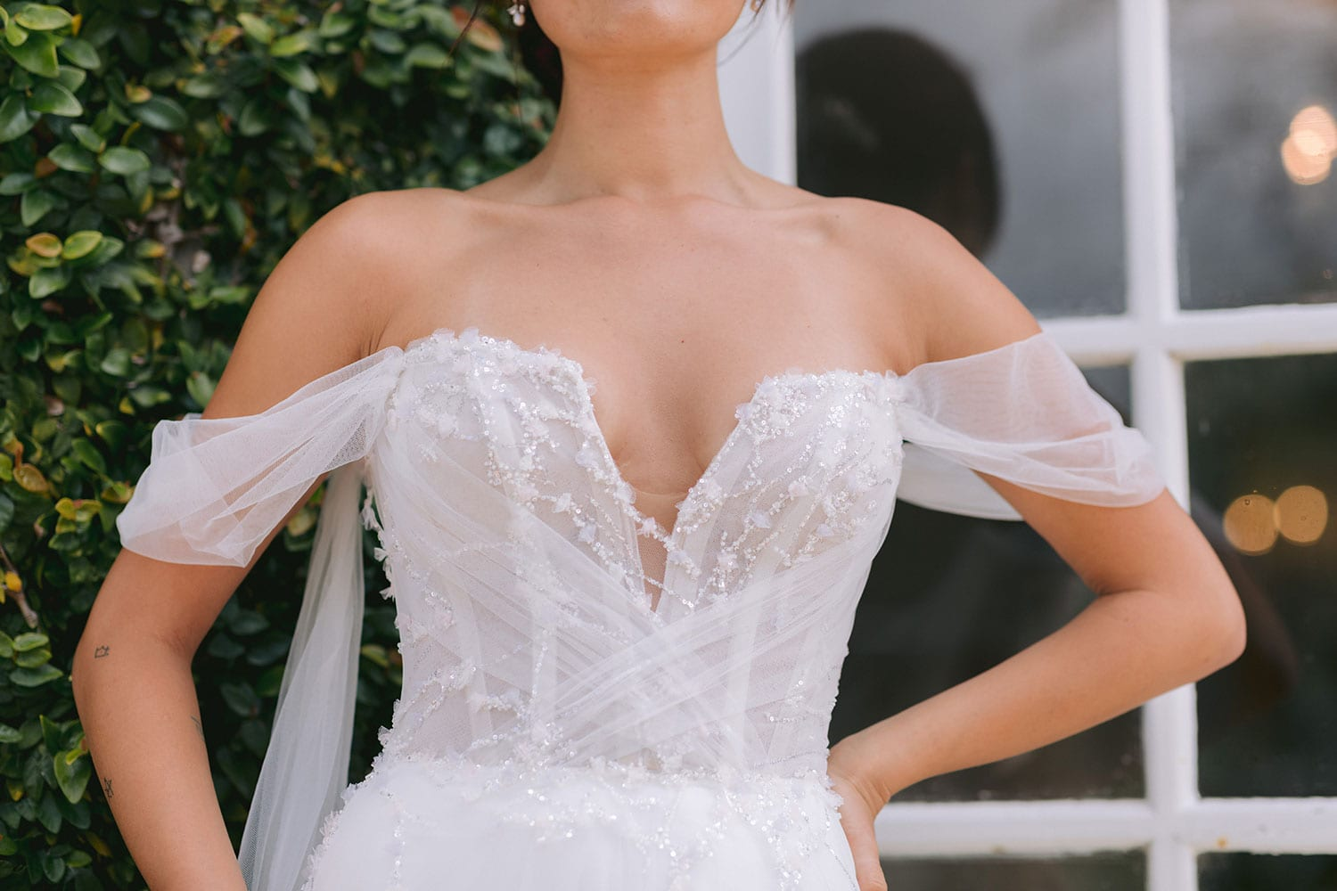 Evie Wedding gown from Vinka Design - Dreamy semi-sheer wedding dress with lace embroidery and beading. The bodice is structured, with hand-appliqued lace and draped with tulle to integrate modern elements with classic design. Model wearing gown close up of bodice lace.
