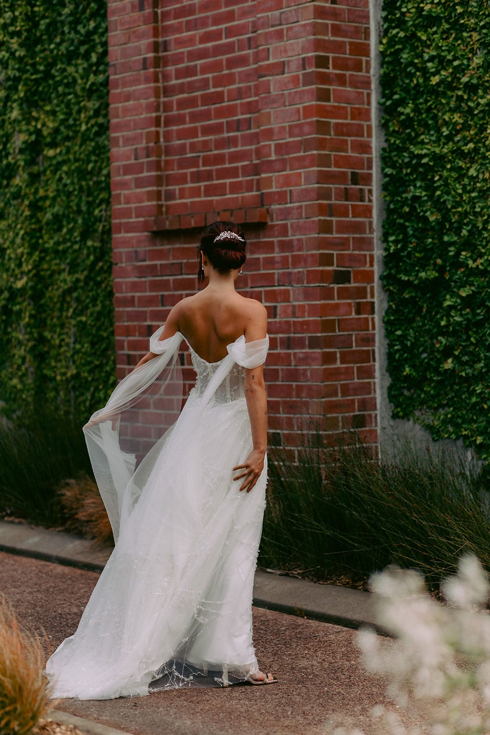 Evie Wedding gown from Vinka Design - Dreamy semi-sheer wedding dress with lace embroidery and beading. The bodice is structured, with hand-appliqued lace and draped with tulle to integrate modern elements with classic design. Model wearing gown portrait walking away with dress flowing.