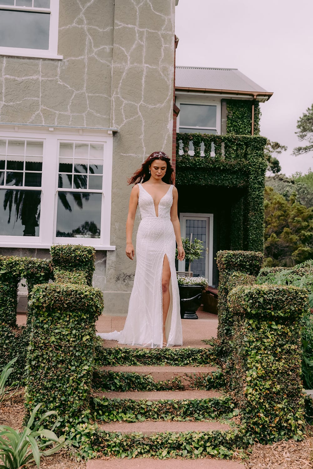 Elle Wedding gown from Vinka Design - Wedding dress with illusion neckline and deep plunge in the front with low back. Stunning beaded embroidery over a stretch base that sculpts and flatters the figure and falls into a beautiful flared train. Model wearing gown in beautiful gardens.