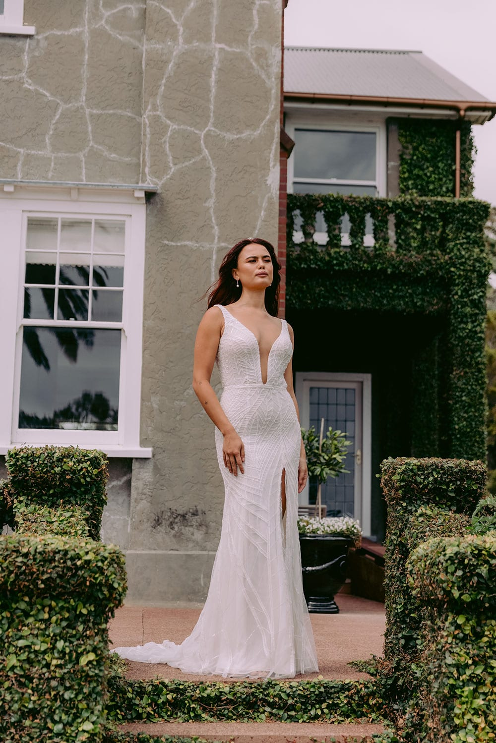 Elle Wedding gown from Vinka Design - Wedding dress with illusion neckline and deep plunge in the front with low back. Stunning beaded embroidery over a stretch base that sculpts and flatters the figure and falls into a beautiful flared train. Model wearing gown on steps in beautiful gardens.