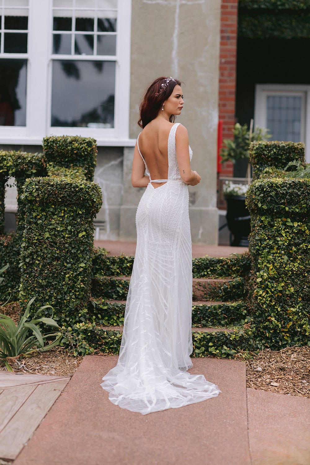 Elle Wedding gown from Vinka Design - Wedding dress with illusion neckline and deep plunge in the front with low back. Stunning beaded embroidery over a stretch base that sculpts and flatters the figure and falls into a beautiful flared train. Model wearing gown in beautiful gardens showing lace train.