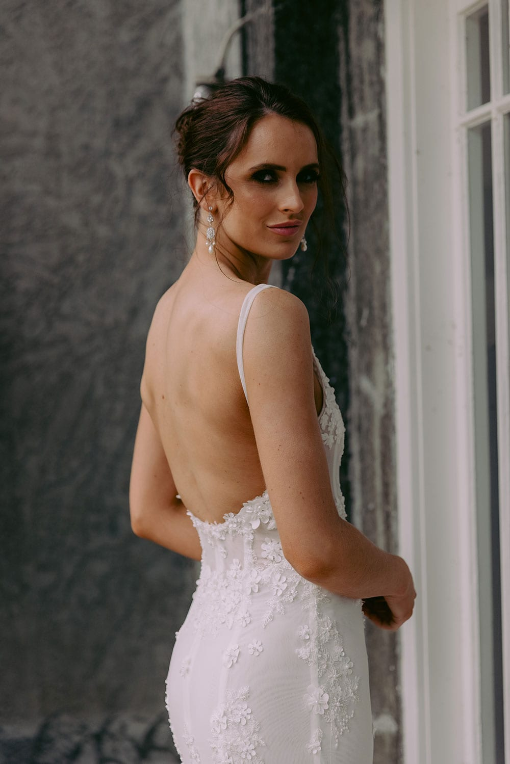 E'more Wedding gown from Vinka Design - This stunning lace wedding gown is hand sewn with a fully beaded 3D flower embroidery. Structured and boned bodice with scoop neckline in the front and low back. Stretch fit skirt flares into full lace train. Model wearing gown outside heritage building showing low back detail.