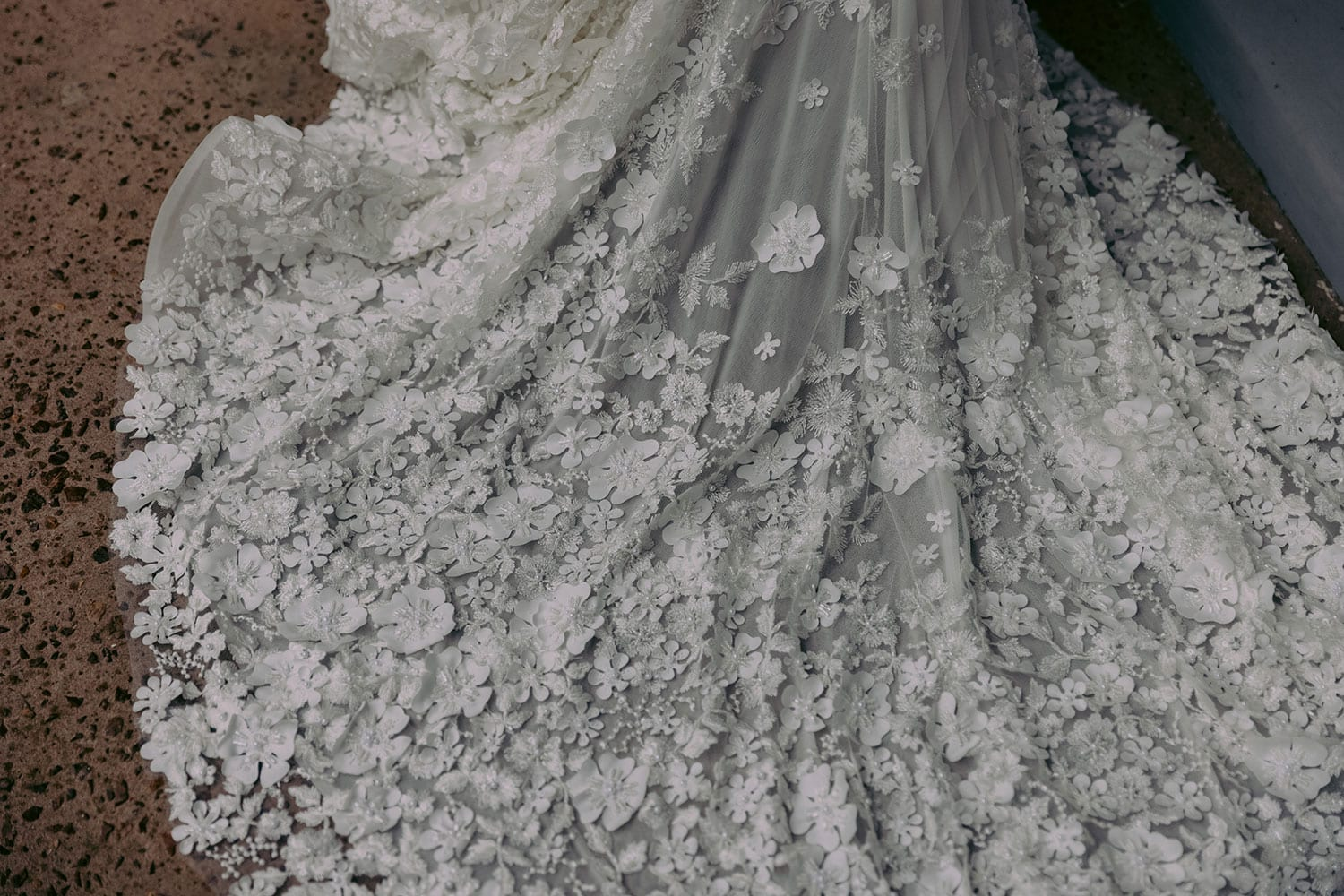 E'more Wedding gown from Vinka Design - This stunning lace wedding gown is hand sewn with a fully beaded 3D flower embroidery. Structured and boned bodice with scoop neckline in the front and low back. Stretch fit skirt flares into full lace train. Full close up detail of hand sewn lace train.