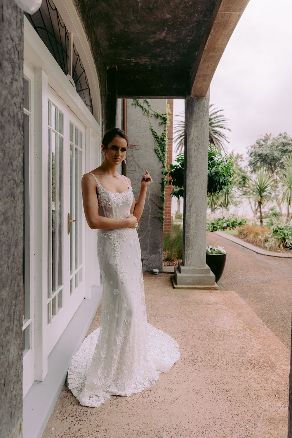 E'more Wedding gown from Vinka Design - This stunning lace wedding gown is hand sewn with a fully beaded 3D flower embroidery. Structured and boned bodice with scoop neckline in the front and low back. Stretch fit skirt flares into full lace train. Model wearing gown outside old heritage building.