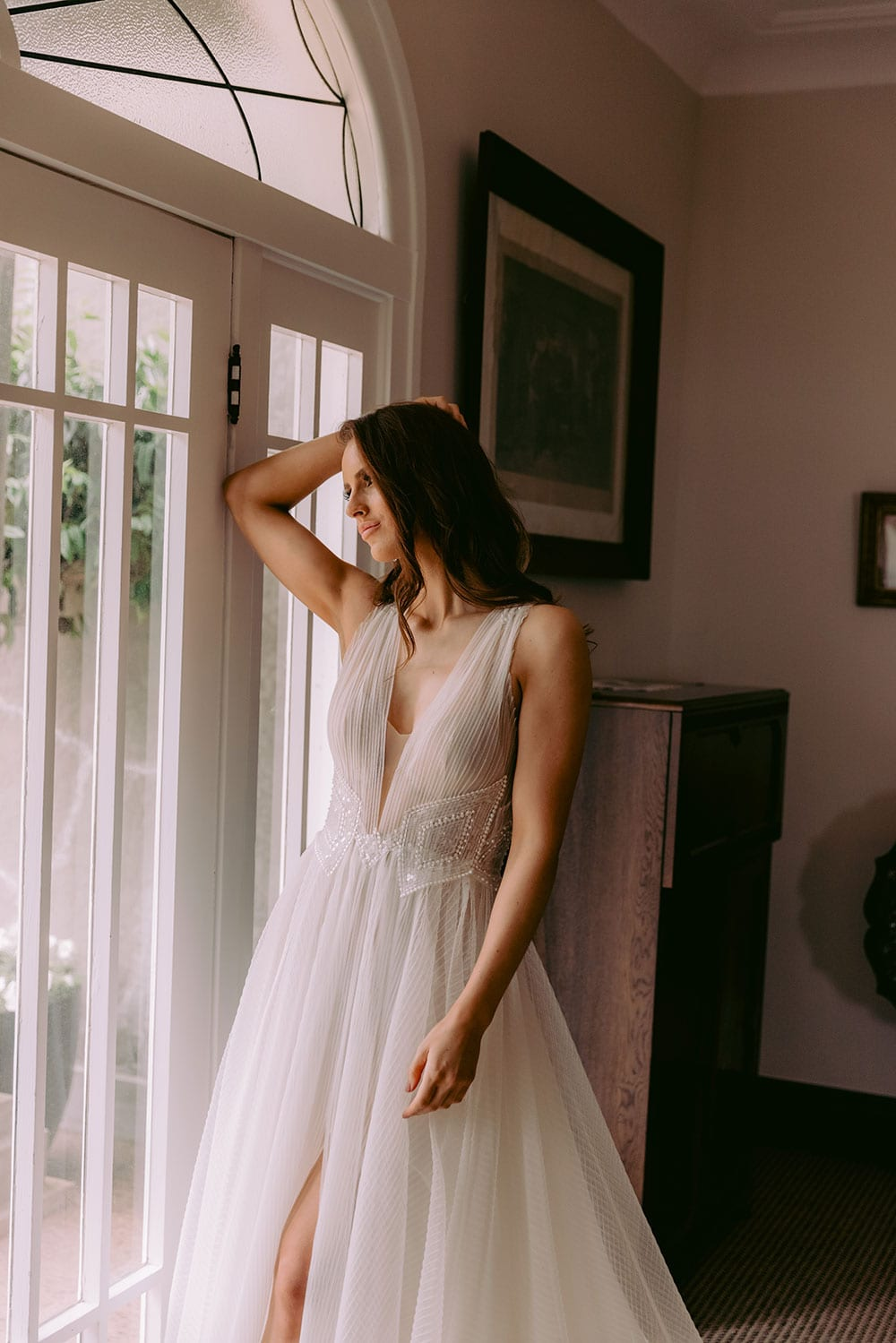 Daytona Wedding gown from Vinka Design - This gown is a true show stopper! Soft pleated tulle wedding dress that cascades into a dramatic train. Tulle or Satin under-skirt accentuates the waist with the perfect combination of hand-beaded sequins and pearls. Model wearing gown inside beautiful old room next to window.