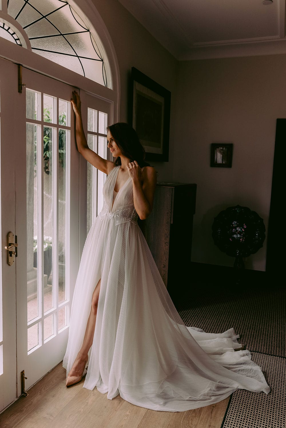 Daytona Wedding gown from Vinka Design - This gown is a true show stopper! Soft pleated tulle wedding dress that cascades into a dramatic train. Tulle or Satin under-skirt accentuates the waist with the perfect combination of hand-beaded sequins and pearls. Model wearing gown inside beautiful old room next to window, train flowing behind.