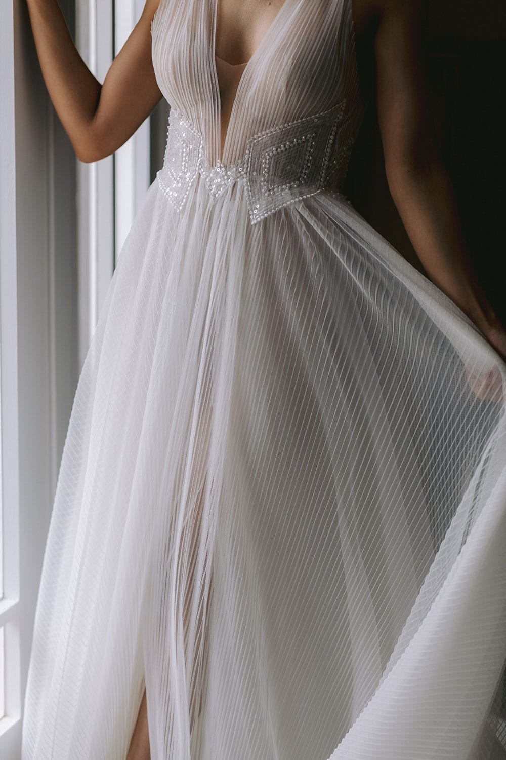 Daytona Wedding gown from Vinka Design - This gown is a true show stopper! Soft pleated tulle wedding dress that cascades into a dramatic train. Tulle or Satin under-skirt accentuates the waist with the perfect combination of hand-beaded sequins and pearls. Model wearing gown next to window, close up detail of skirt.