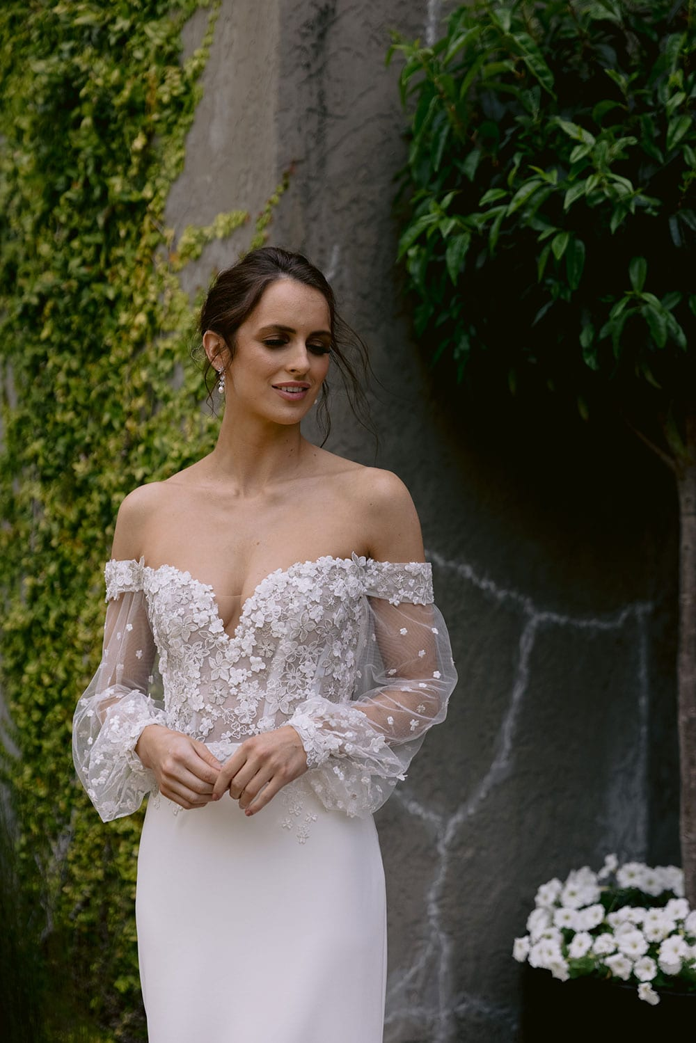 Chloe Wedding gown from Vinka Design - Wedding gown with 3D embellished platinum and ivory flower lace, complemented by stunning off-shoulder straps. A semi-sheer bodice trails into a gorgeous stretch crepe skirt that hugs the figure in all the right places. Model wearing gown in gardens.