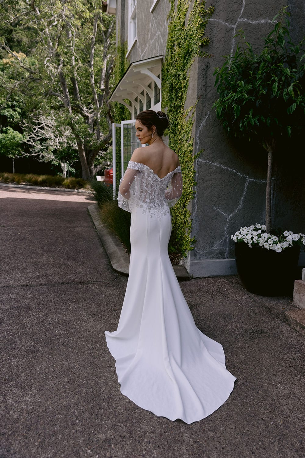 Chloe Wedding gown from Vinka Design - Wedding gown with 3D embellished platinum and ivory flower lace, complemented by stunning off-shoulder straps. A semi-sheer bodice trails into a gorgeous stretch crepe skirt that hugs the figure in all the right places. Model wearing gown in gardens with train.