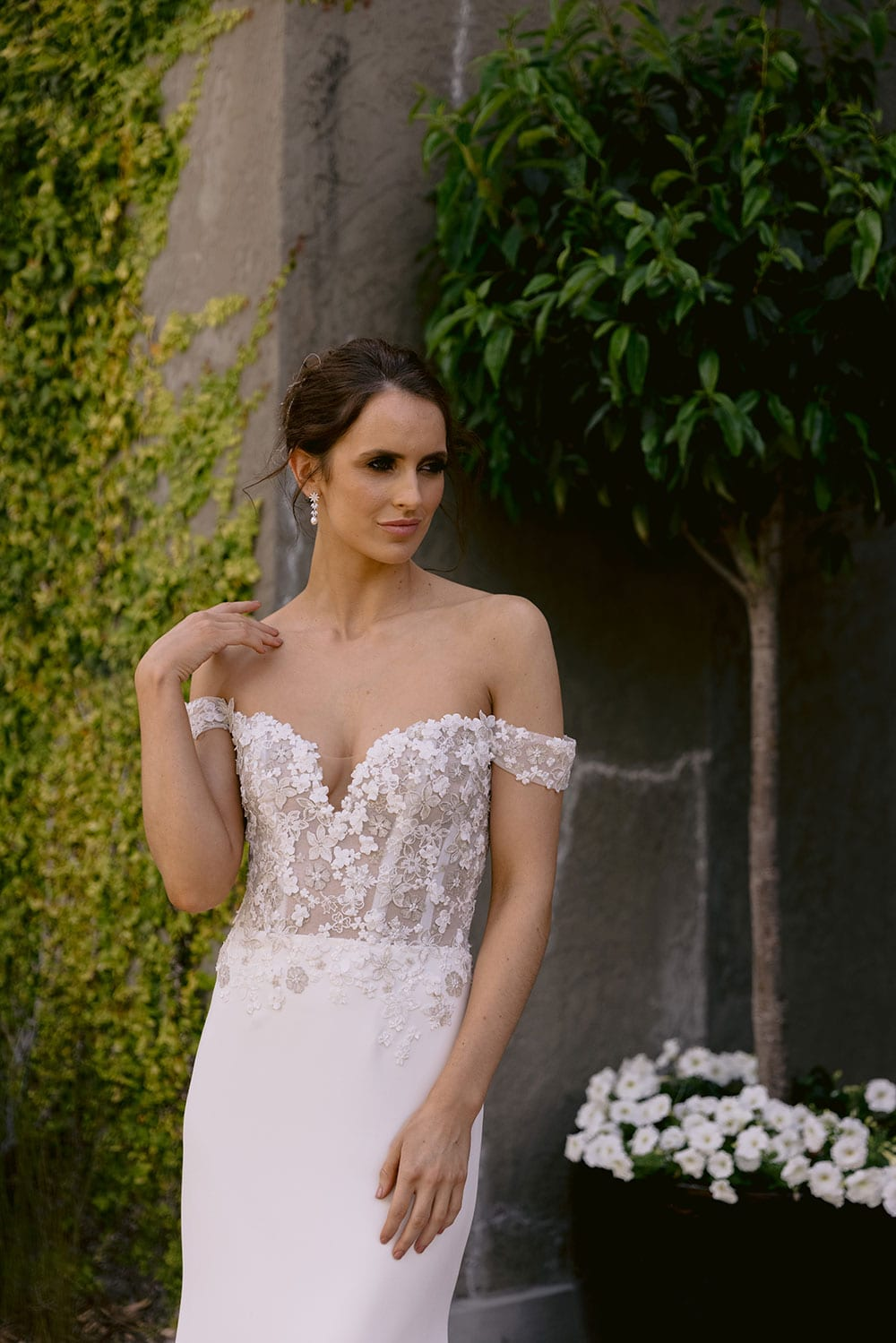 Chloe Wedding gown from Vinka Design - Wedding gown with 3D embellished platinum and ivory flower lace, complemented by stunning off-shoulder straps. A semi-sheer bodice trails into a gorgeous stretch crepe skirt that hugs the figure in all the right places. Model wearing gown in gardens detail of low V front of dress.